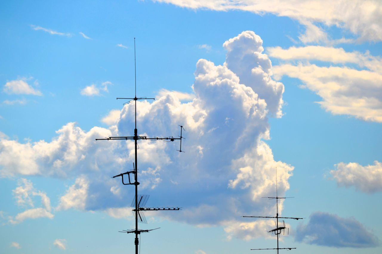 Low Angle View Of Antennas Against Cloudy Sky