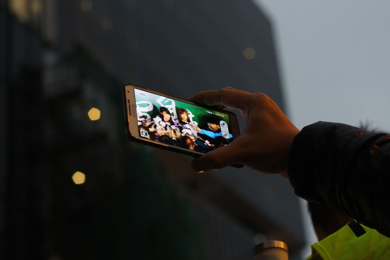 real people, leisure activity, event, human hand, men, night, holding, lifestyles, technology, photographing, device screen, wireless technology, communication, nightlife, photography themes, togetherness, human body part, outdoors, illuminated, modern, crowd, close-up, people