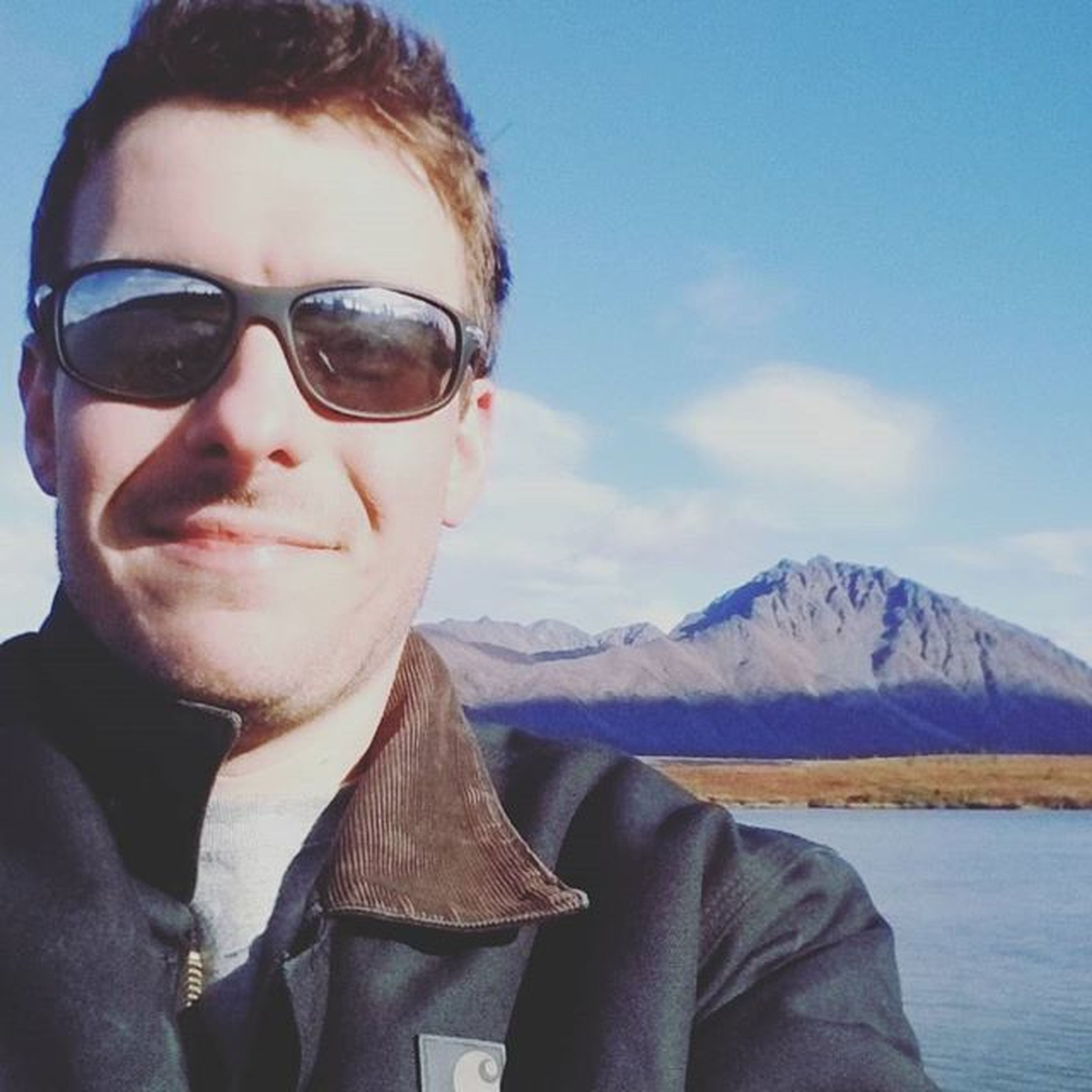 winter, lifestyles, looking at camera, person, portrait, cold temperature, young adult, leisure activity, snow, young men, headshot, mountain, front view, sky, sunglasses, warm clothing, smiling, casual clothing