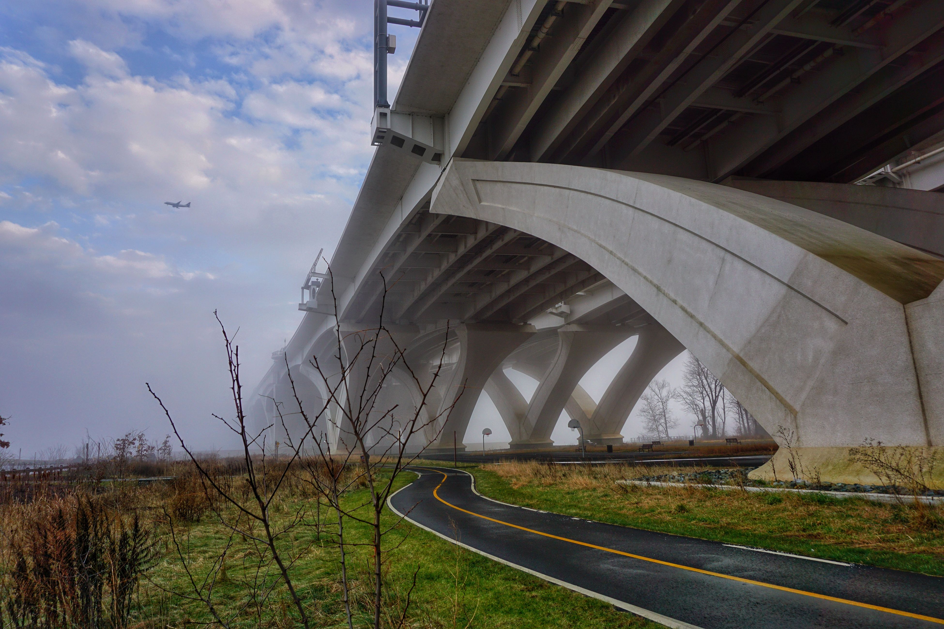 built structure, architecture, sky, transportation, the way forward, railroad track, cloud - sky, grass, field, rail transportation, abandoned, diminishing perspective, day, cloud, no people, building exterior, connection, outdoors, vanishing point, plant