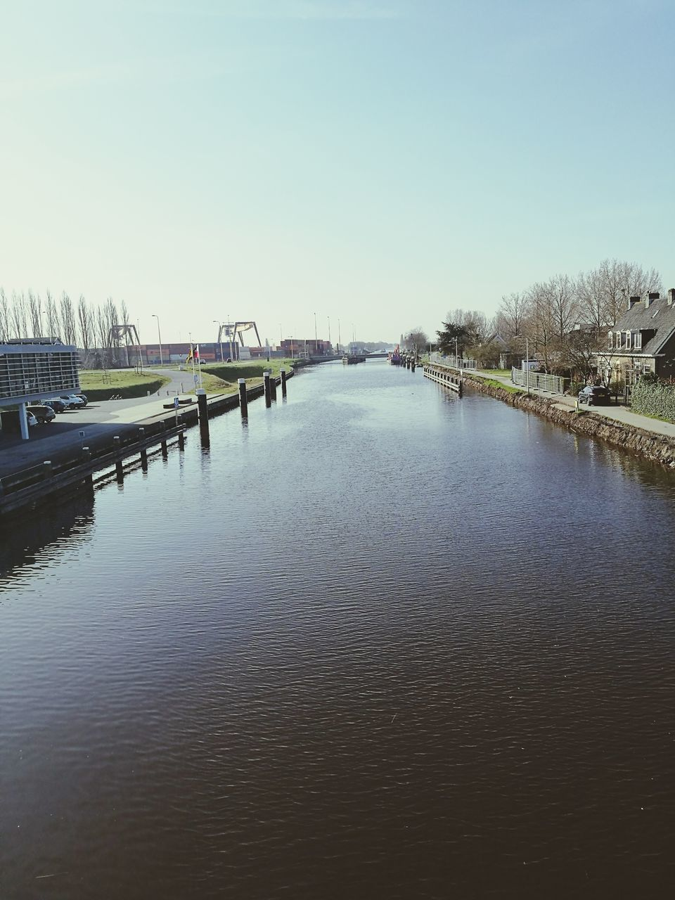 river, water, architecture, bridge - man made structure, connection, built structure, outdoors, waterfront, building exterior, no people, day, city, sky, clear sky, nature, tree, cityscape