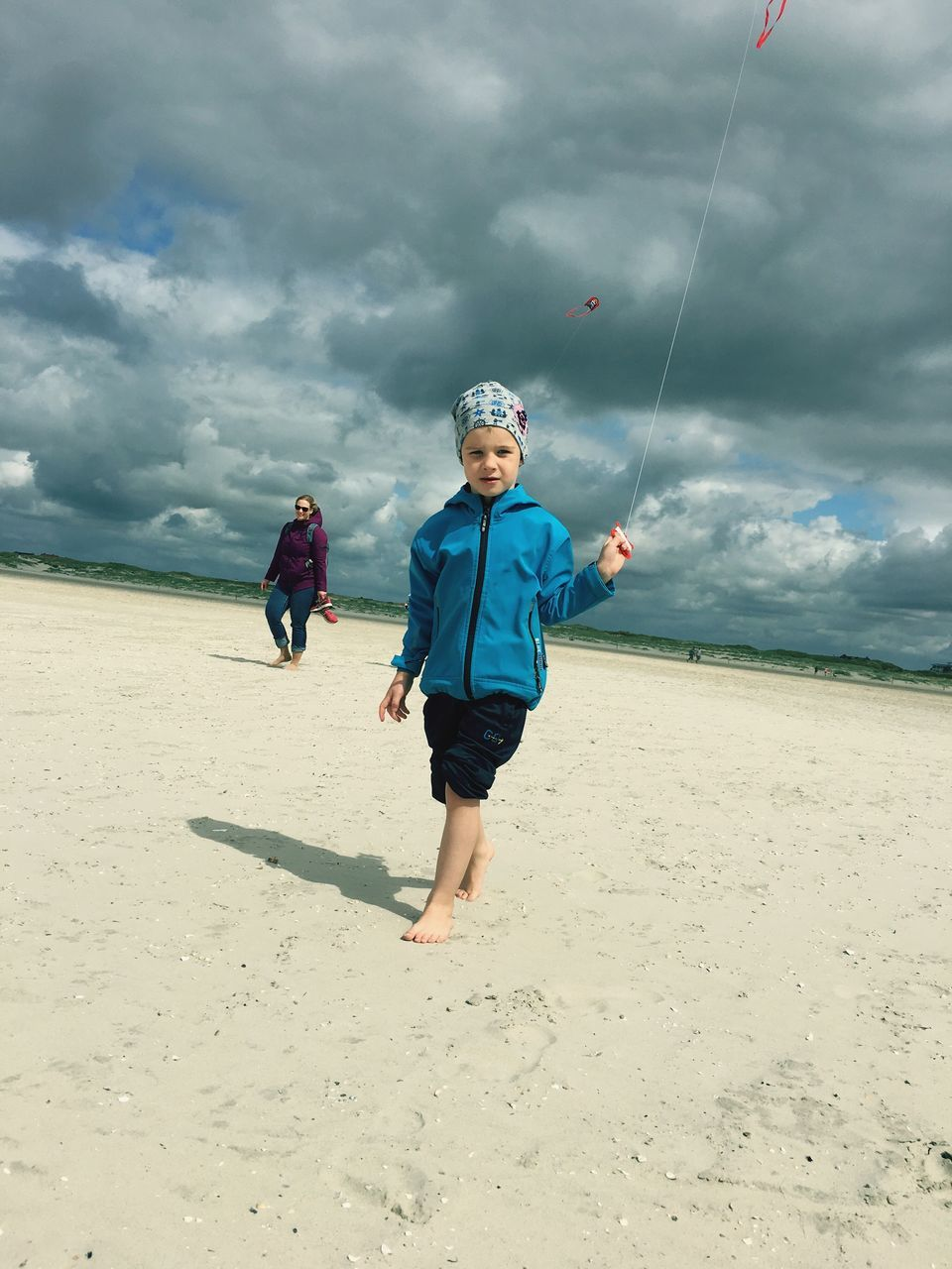 boys, childhood, full length, sand, sky, cloud - sky, leisure activity, beach, outdoors, real people, front view, looking at camera, sea, elementary age, day, two people, nature, senior adult, happiness, motion, togetherness, standing, adventure, portrait, people
