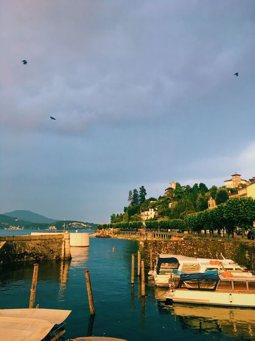 Storm clouds gather over a small boat harbor, Italy. Beauty In Nature Boats Cloudy Golden Hour Harbor Harbor View Idylic Scene Italy Lake Light Moorings  Nature Old Harbour Storm Storm Clouds Trees And Sky Waterway