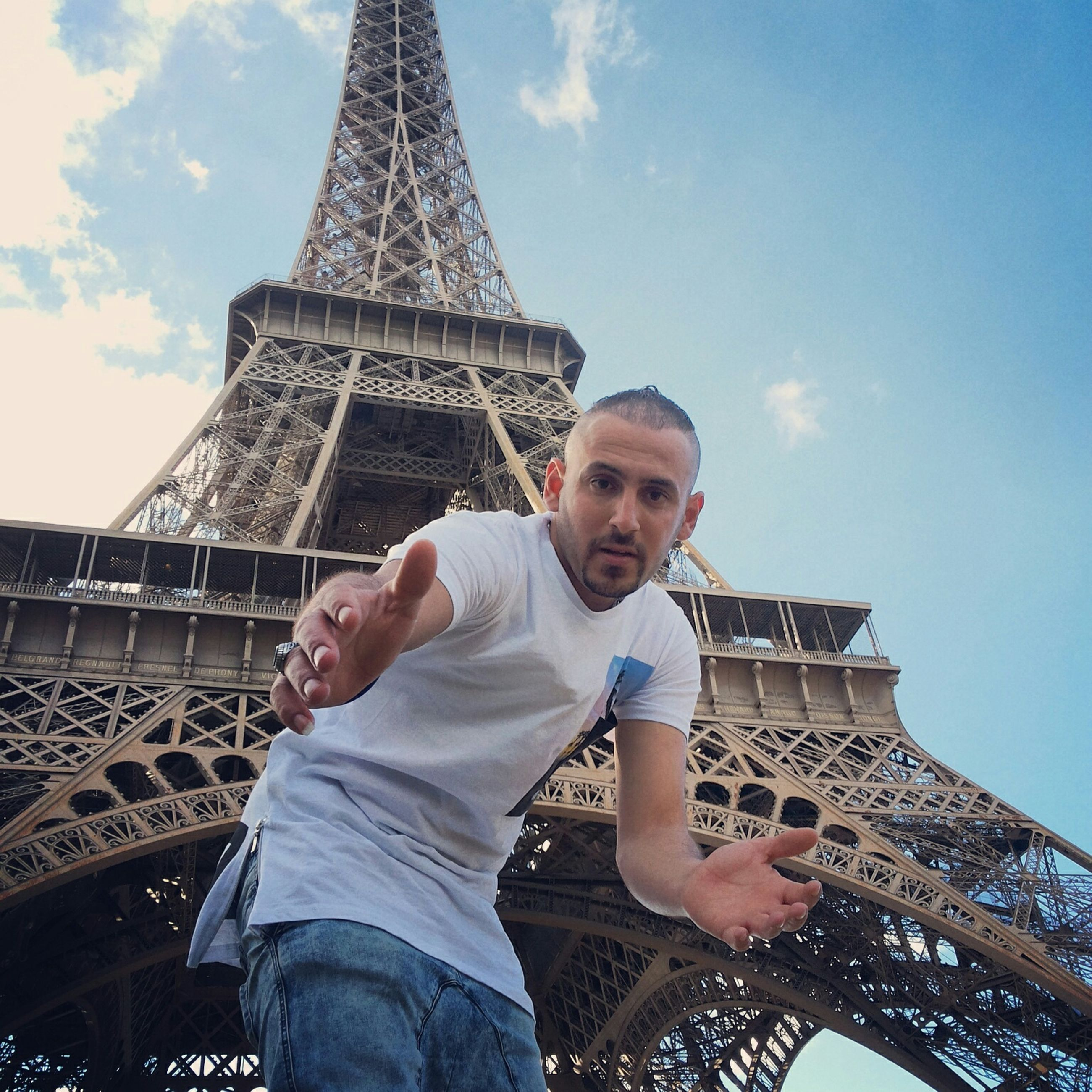 low angle view, built structure, architecture, lifestyles, leisure activity, casual clothing, sky, famous place, tall - high, capital cities, tower, eiffel tower, person, tourism, international landmark, travel destinations, travel, metal