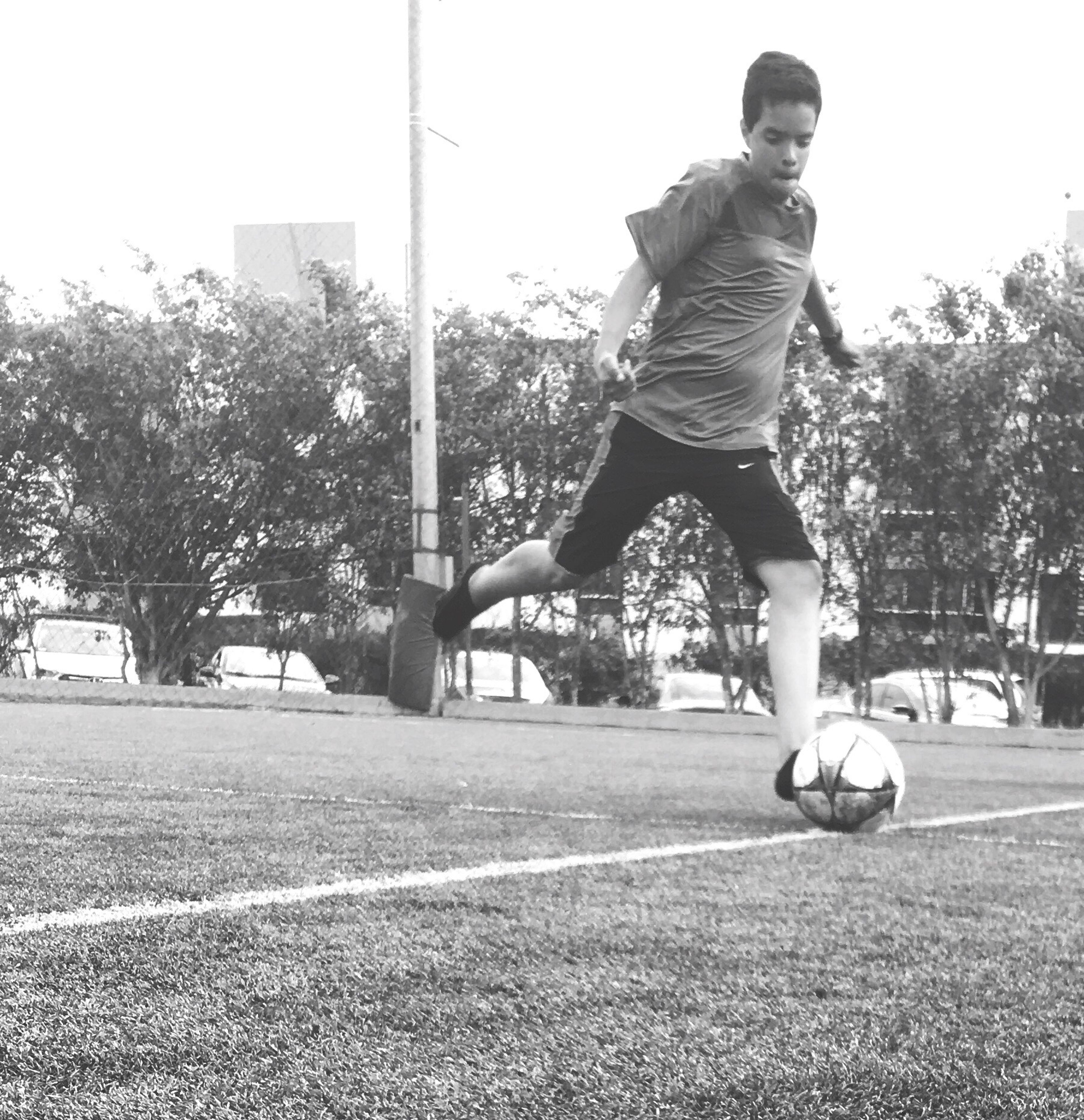 full length, mid-air, jumping, soccer, one person, sport, motion, park - man made space, soccer ball, kicking, playing, outdoors, childhood, ball, tree, skill, day, people, adult, young adult