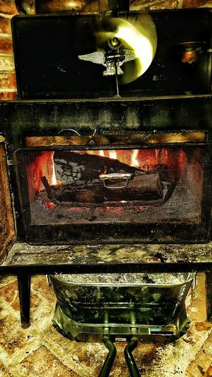 Wood stove with doors open to heat up the house on a cold, damp winter night in February. Burning Wood Heat Source Heat - Temperature Cold Night Cabin Adirondacks Saranac Lake Soothing Wintertime Bright Light Relaxing Enjoying Life Cold Weather Old-fashioned Winter Open Flame Woodstove Burning Bricks Flames Fireplace Seasoned Wood Cast Iron Metal Comfortable