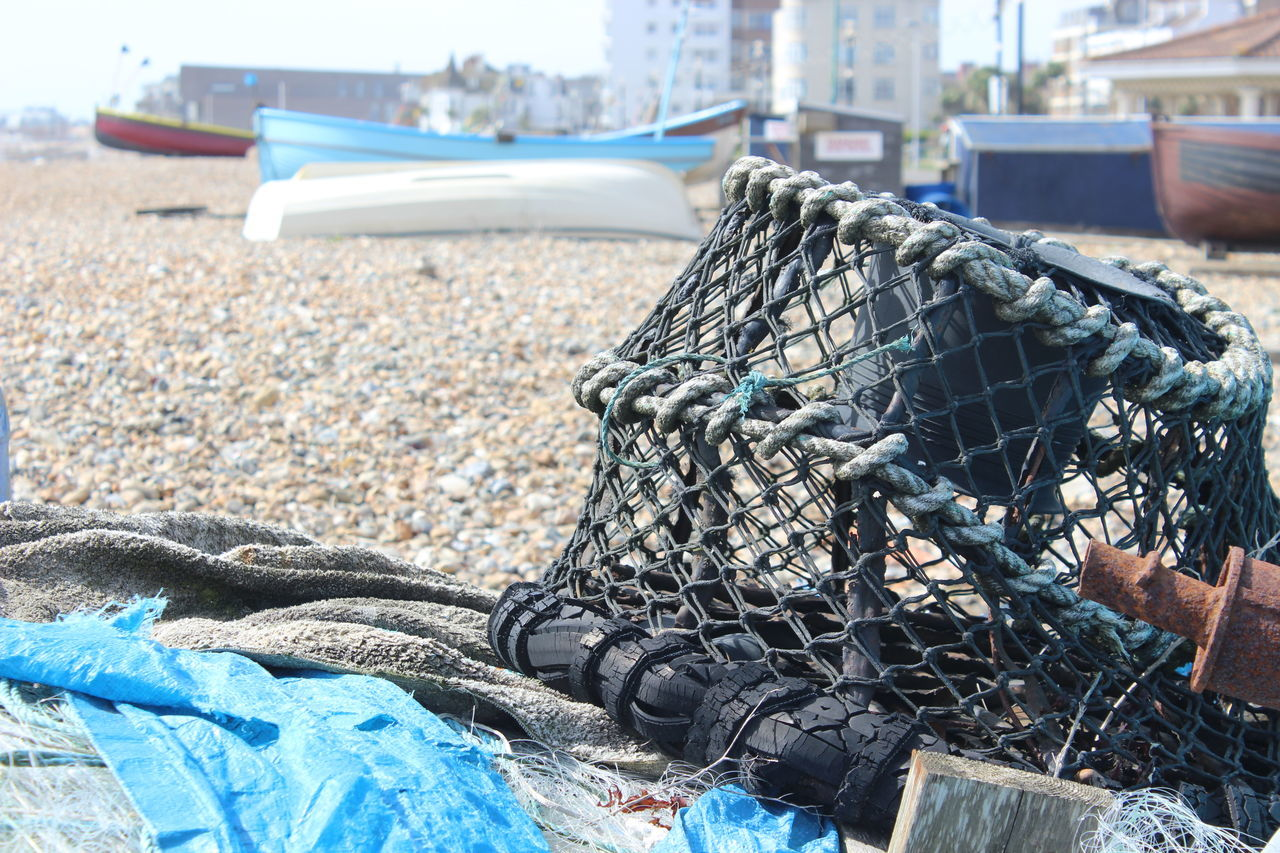 fishing net, rope, day, mode of transport, transportation, nautical vessel, outdoors, beach, real people, focus on foreground, one person, fishing equipment, human hand, human body part, harbor, close-up, water
