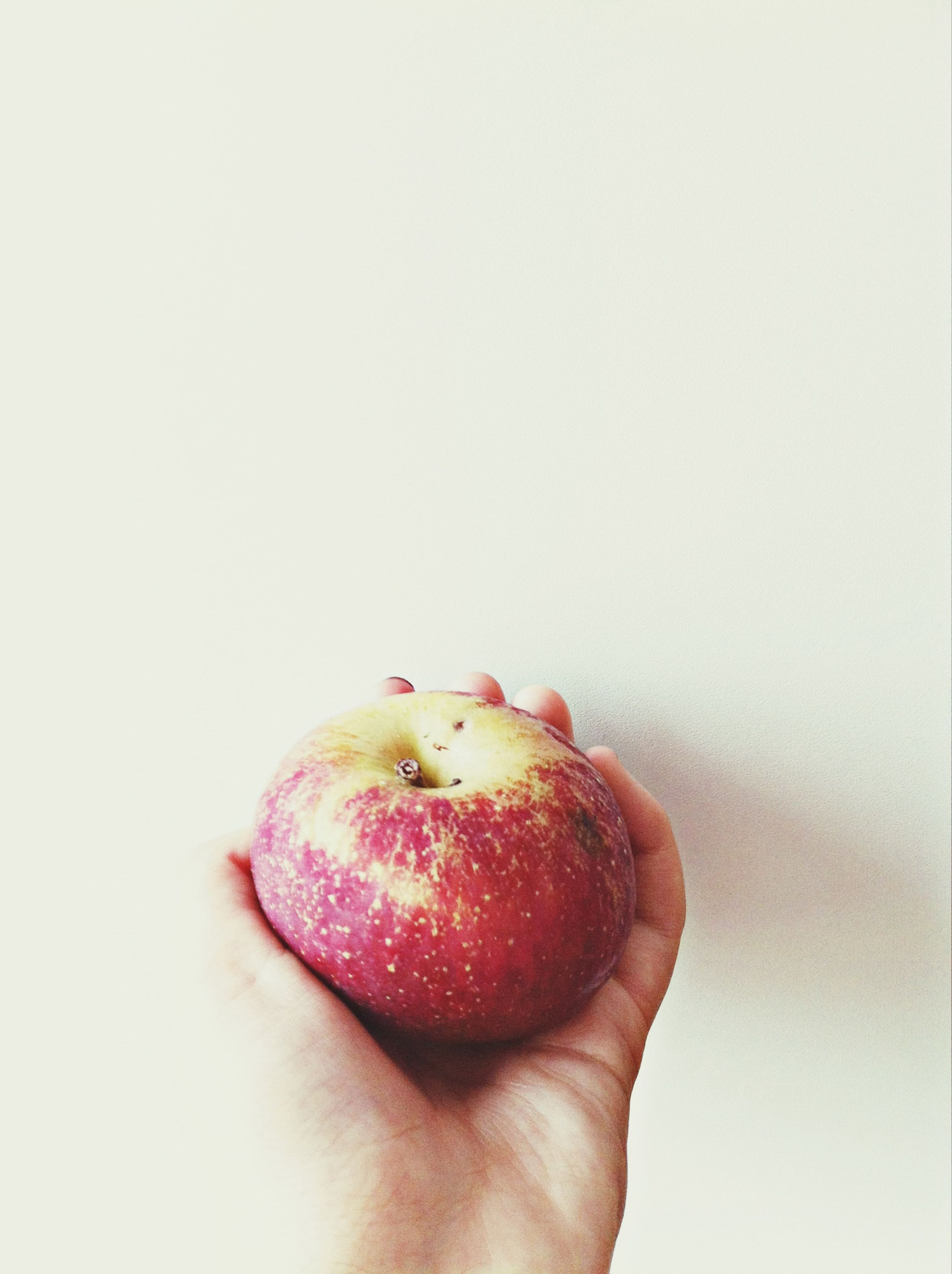 person, studio shot, white background, red, part of, close-up, copy space, cropped, food and drink, fruit, holding, food, human finger, indoors, healthy eating, unrecognizable person, single object