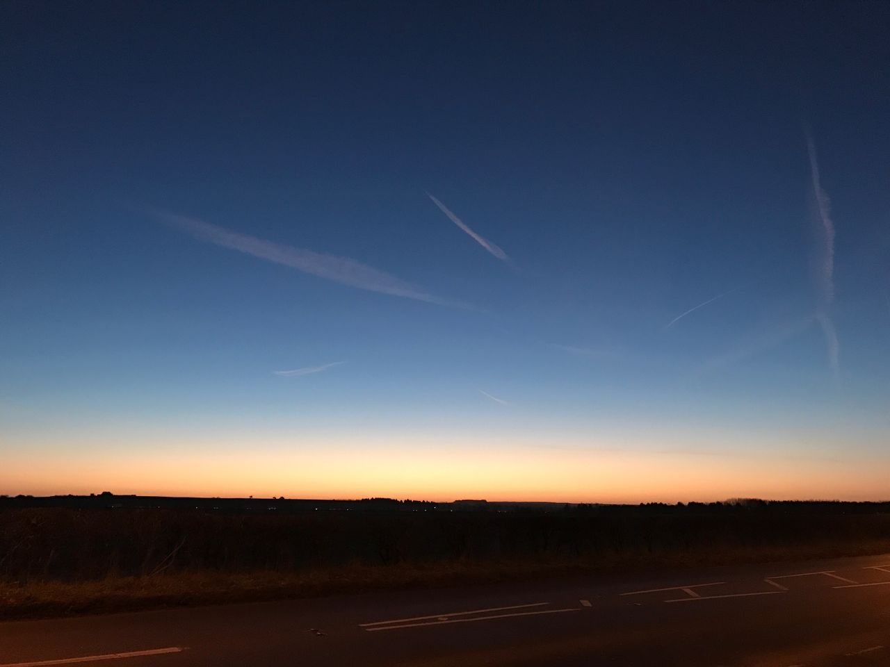 no people, sky, nature, landscape, vapor trail, scenics, sunset, transportation, tranquility, tranquil scene, outdoors, beauty in nature, silhouette, blue, road, clear sky, contrail, day