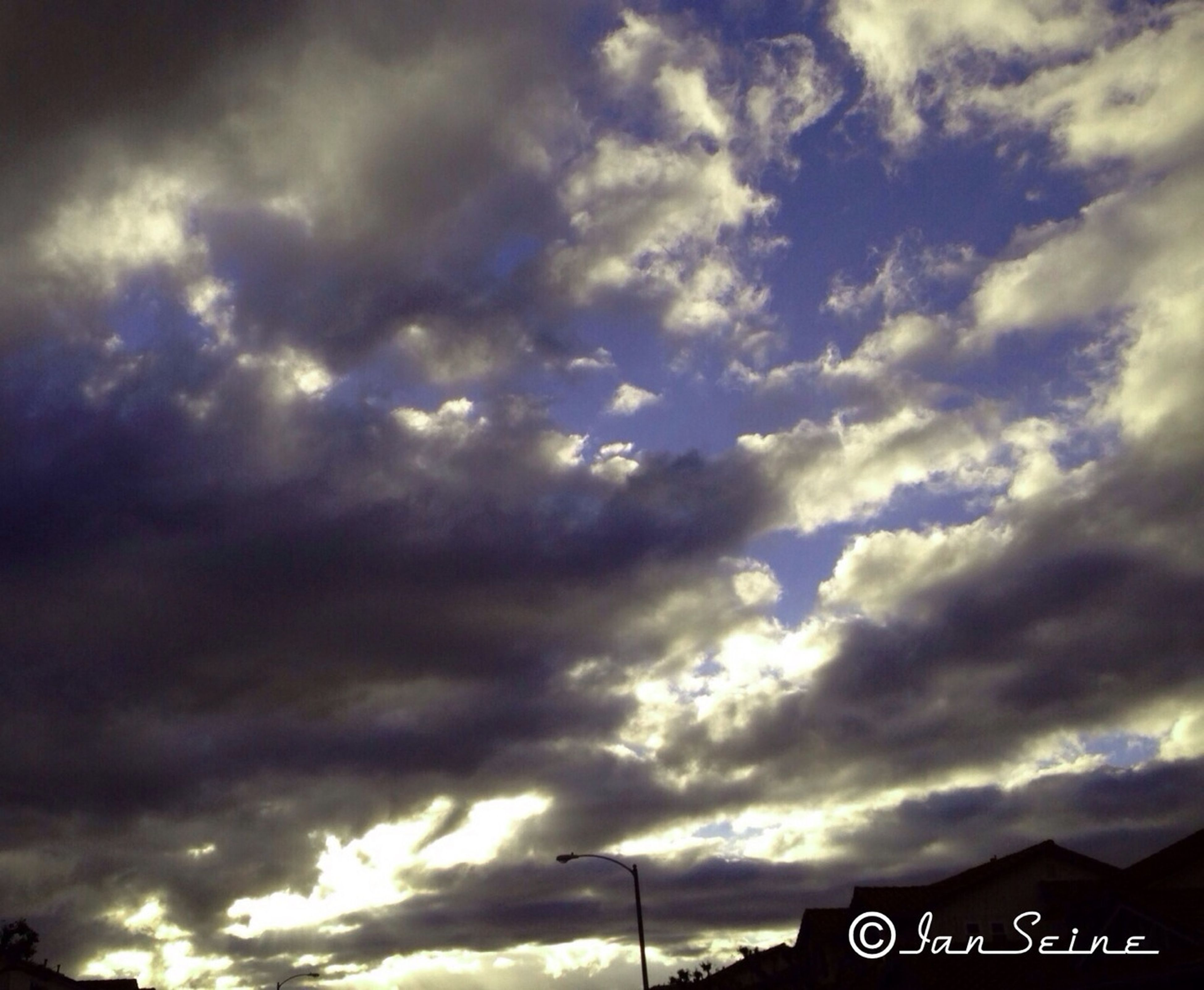 sky, cloud - sky, communication, text, cloudy, low angle view, western script, cloud, information sign, sunset, sign, road sign, weather, cloudscape, nature, tranquility, overcast, scenics, guidance, capital letter