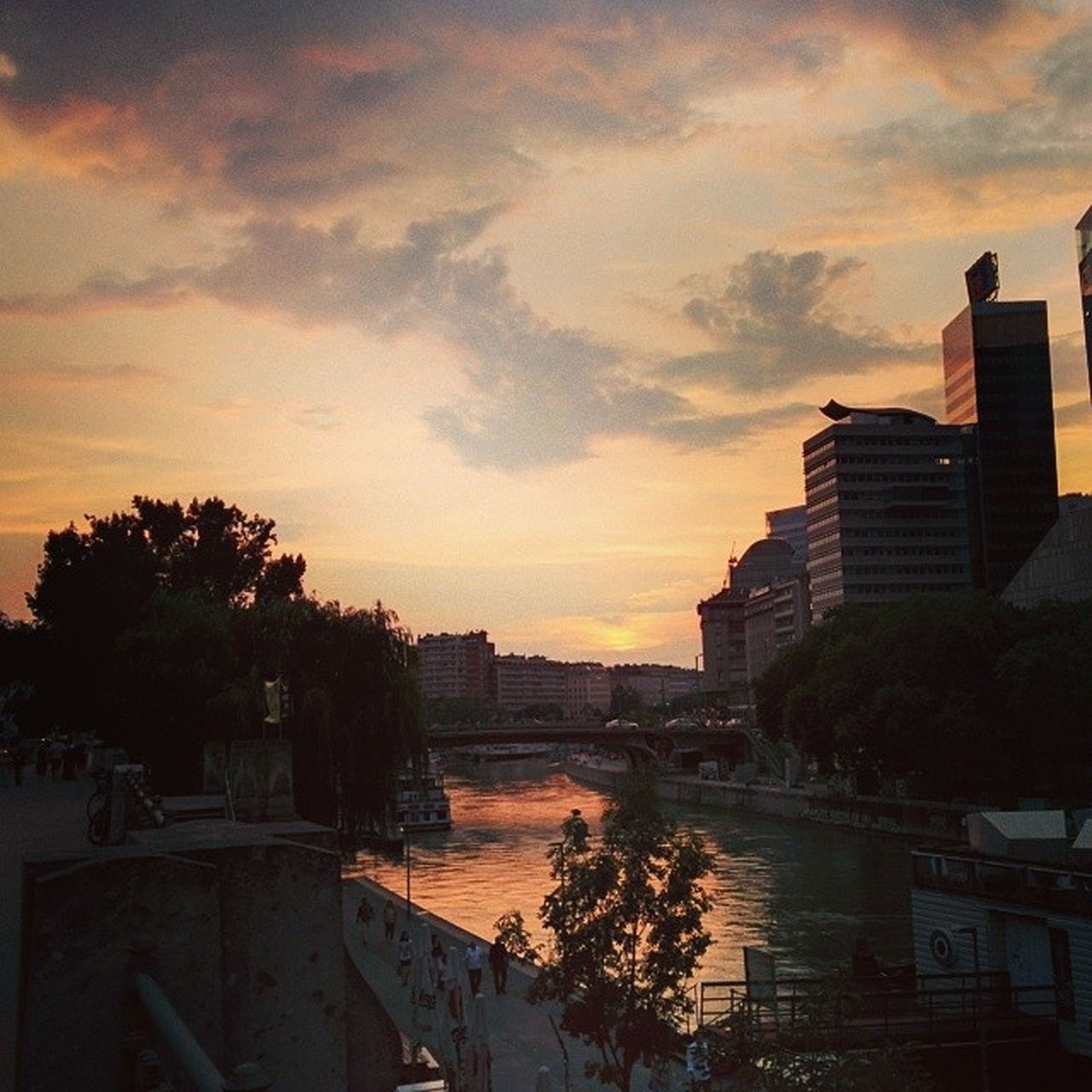 sunset, architecture, building exterior, built structure, sky, tree, cloud - sky, water, city, orange color, river, cloudy, nature, beauty in nature, transportation, railing, cloud, outdoors, residential building, high angle view