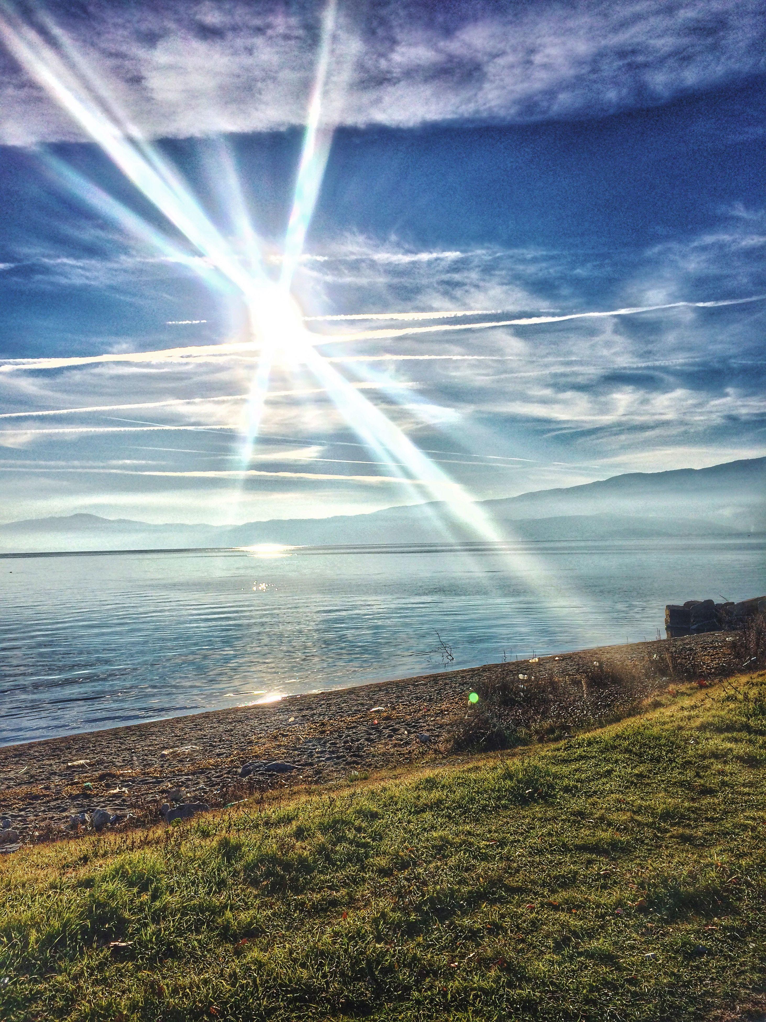 water, tranquil scene, scenics, beauty in nature, sunbeam, sky, sun, tranquility, sunlight, sea, horizon over water, nature, lens flare, idyllic, blue, grass, cloud - sky, sunny, landscape, day