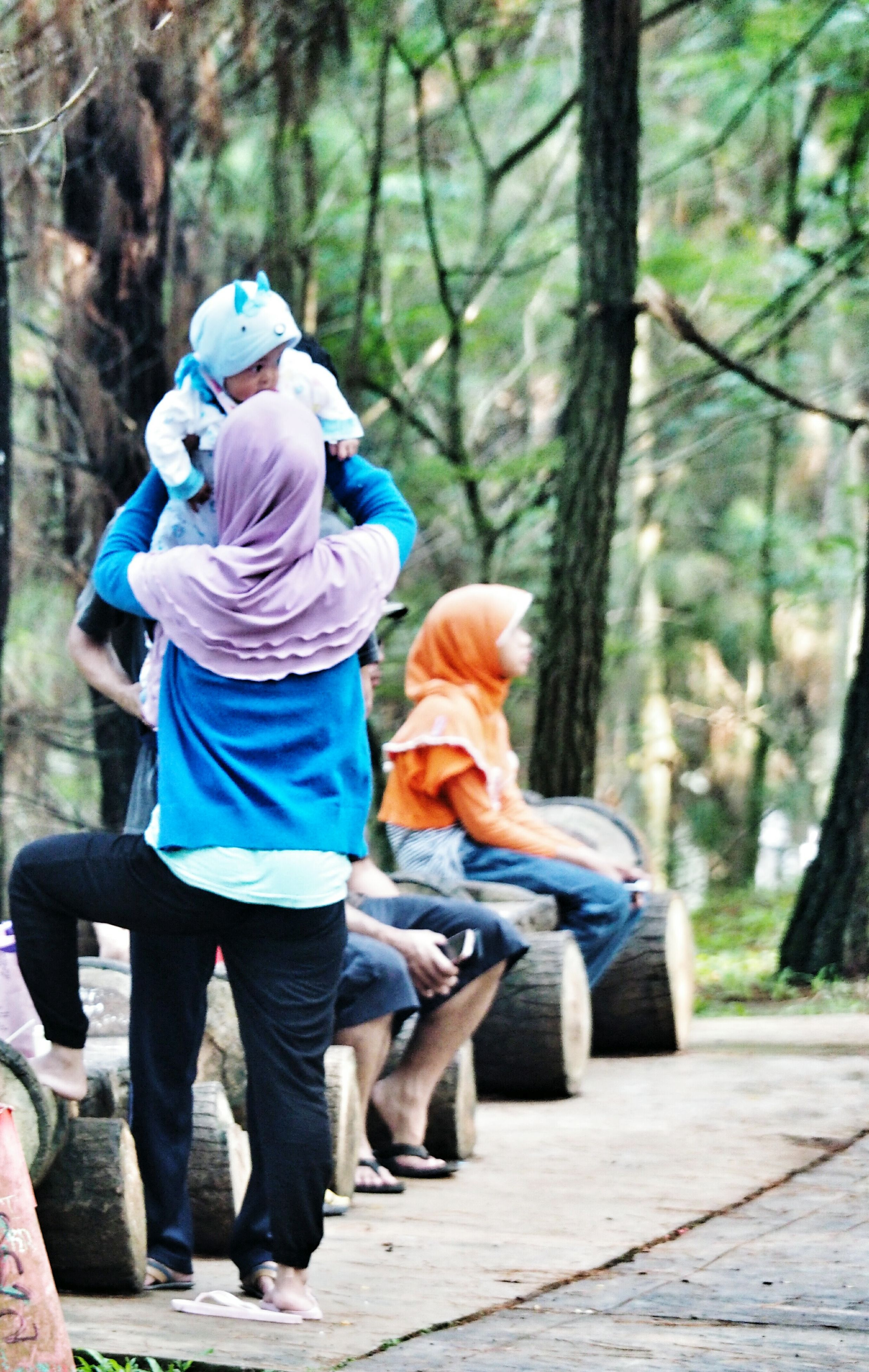 lifestyles, leisure activity, focus on foreground, rear view, tree, childhood, casual clothing, full length, girls, togetherness, boys, person, men, park - man made space, elementary age, sitting, bonding