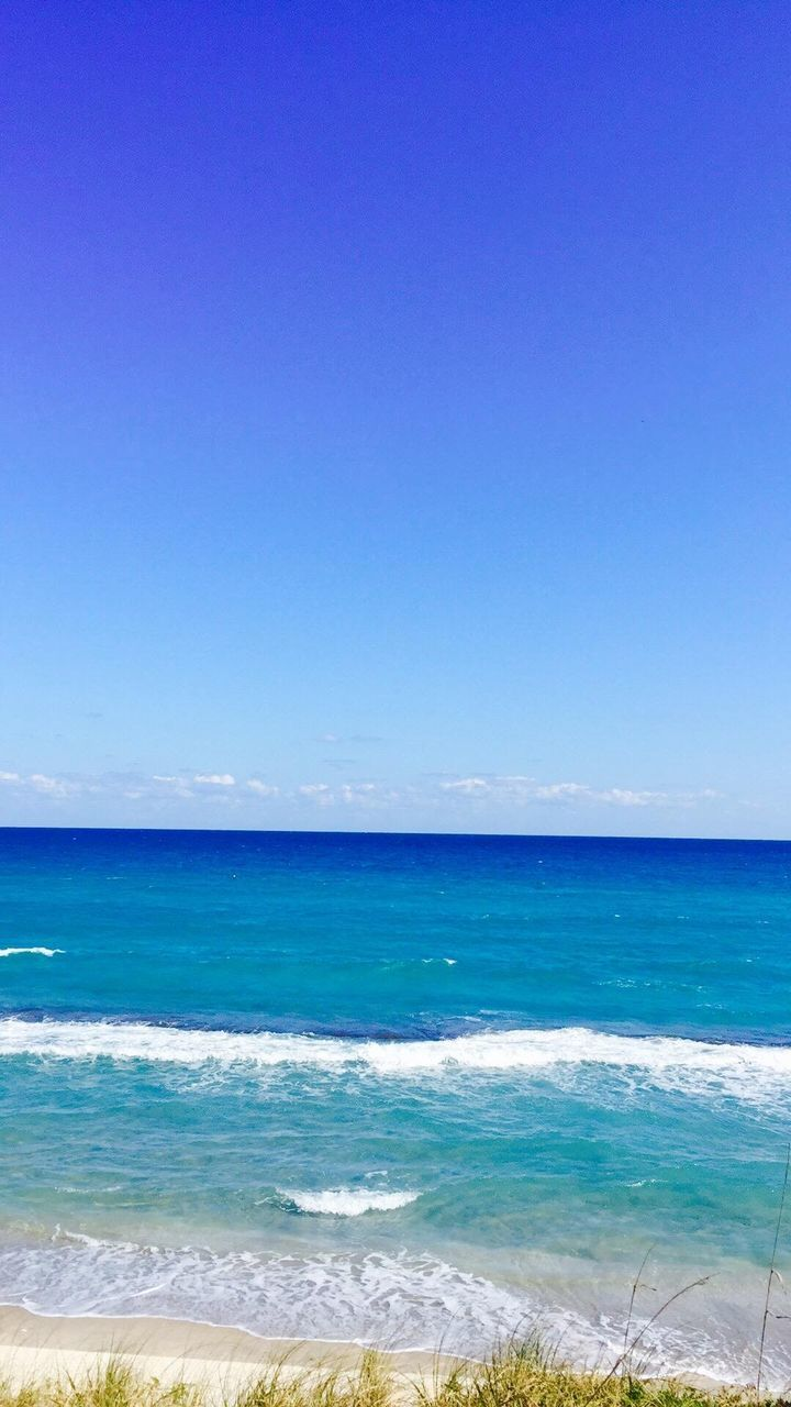 sea, beach, horizon over water, beauty in nature, scenics, blue, nature, water, wave, tranquility, day, clear sky, tranquil scene, outdoors, no people, vacations, sky