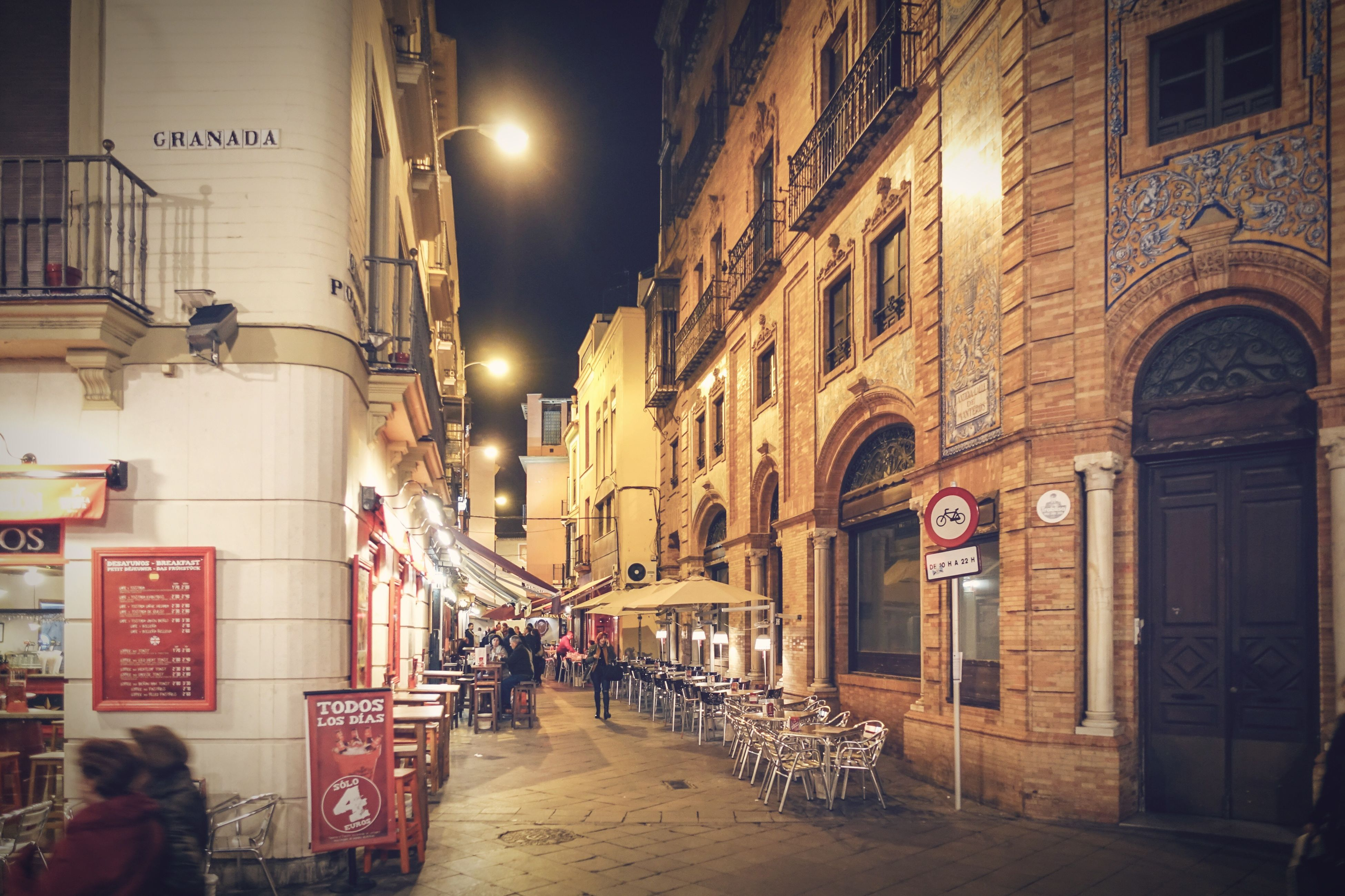 building exterior, architecture, built structure, illuminated, night, street, city, the way forward, street light, lighting equipment, building, text, walking, residential building, city life, incidental people, residential structure, alley, city street