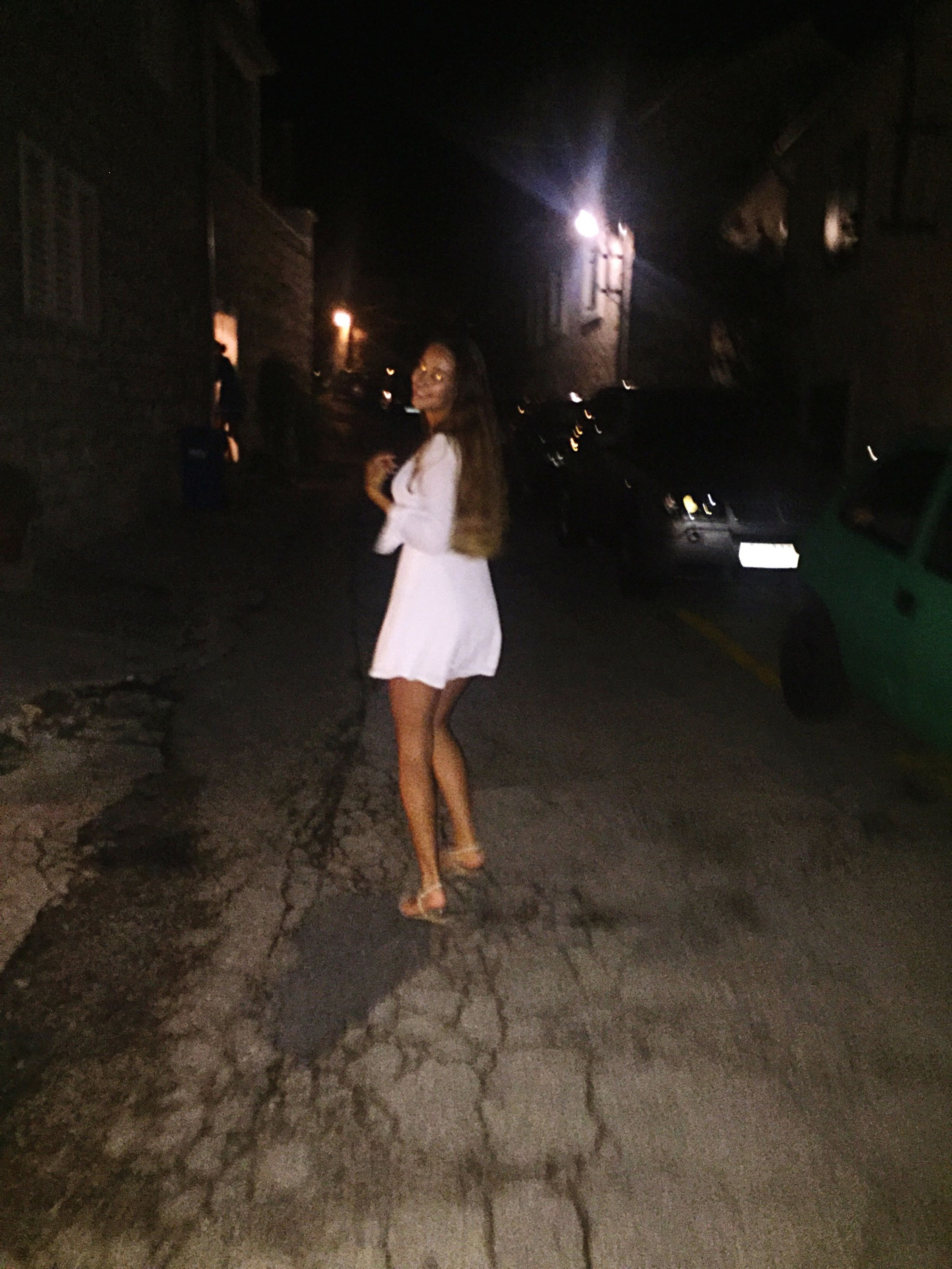 night, illuminated, street, full length, lifestyles, leisure activity, walking, casual clothing, architecture, building exterior, road, built structure, standing, outdoors, person, footpath, in front of, city life, young adult