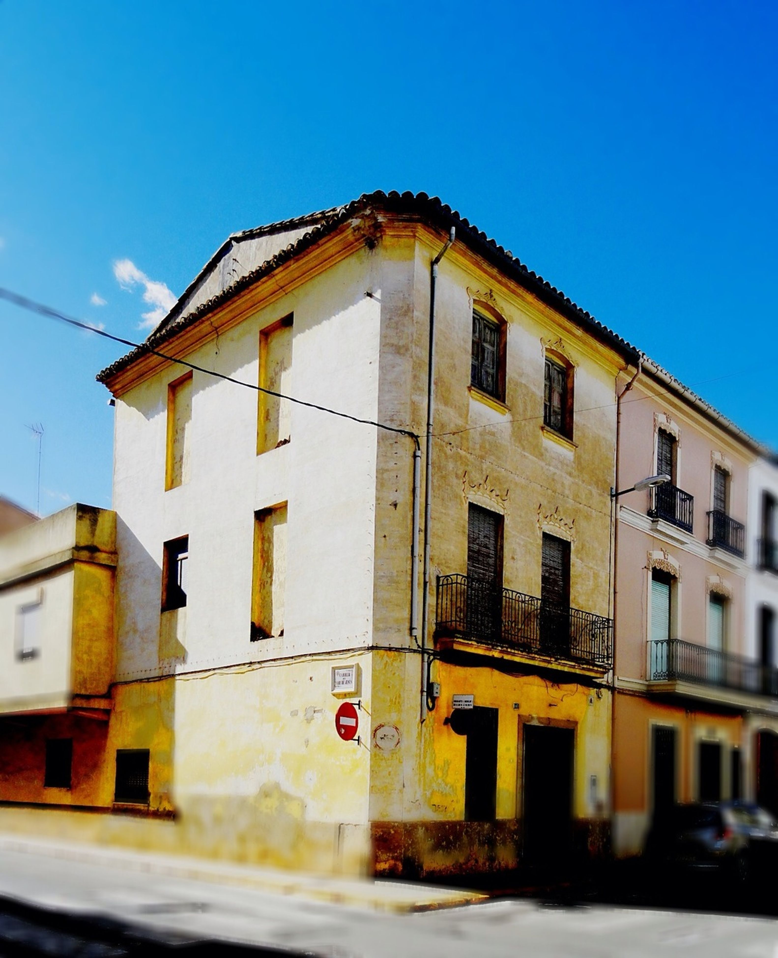 building exterior, architecture, built structure, clear sky, window, blue, residential structure, residential building, house, street, building, day, outdoors, city, sky, road, sunlight, transportation, no people, low angle view