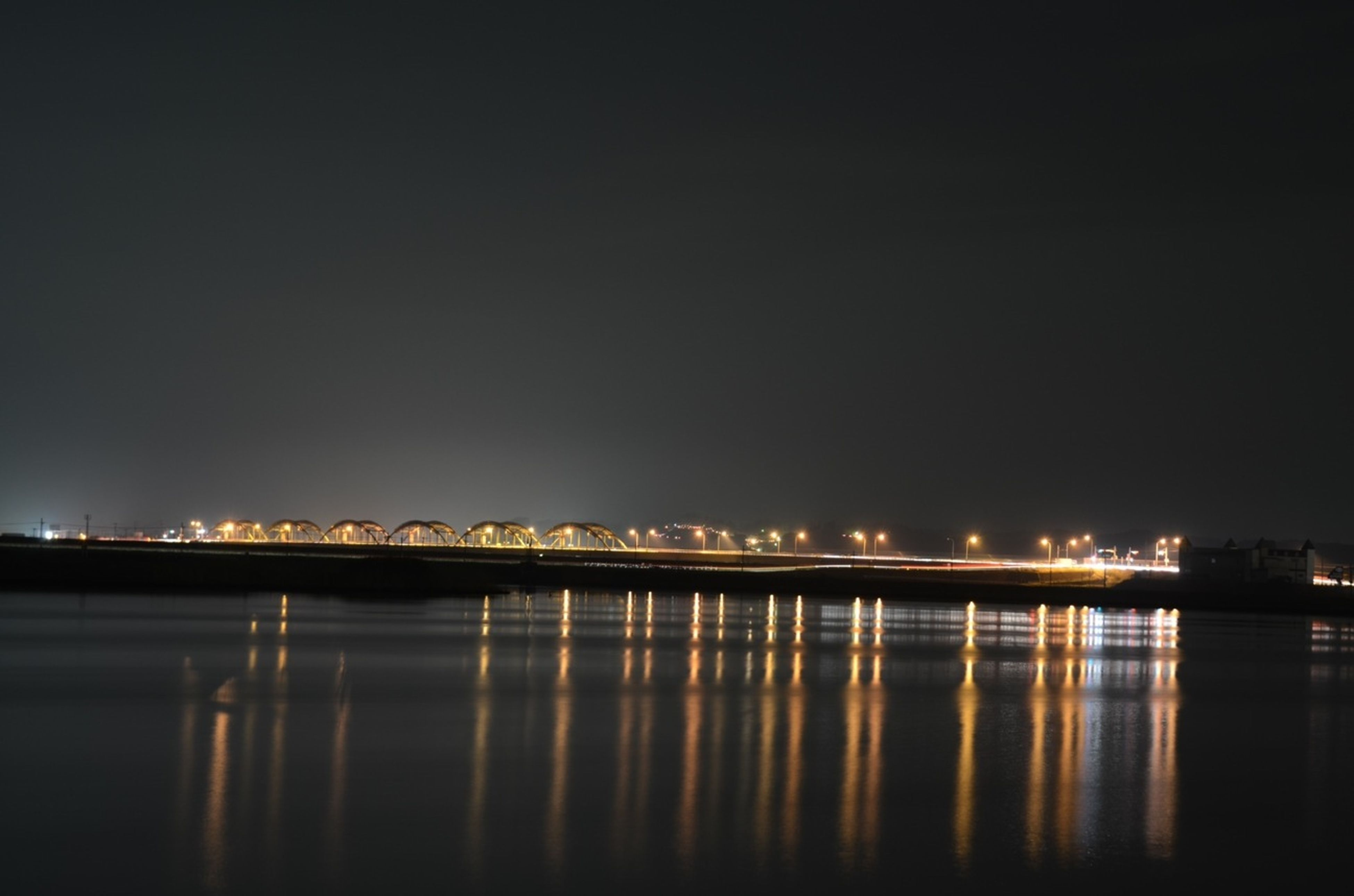 illuminated, night, water, waterfront, reflection, copy space, clear sky, built structure, architecture, river, sea, city, sky, tranquil scene, tranquility, building exterior, light, scenics, connection, bridge - man made structure