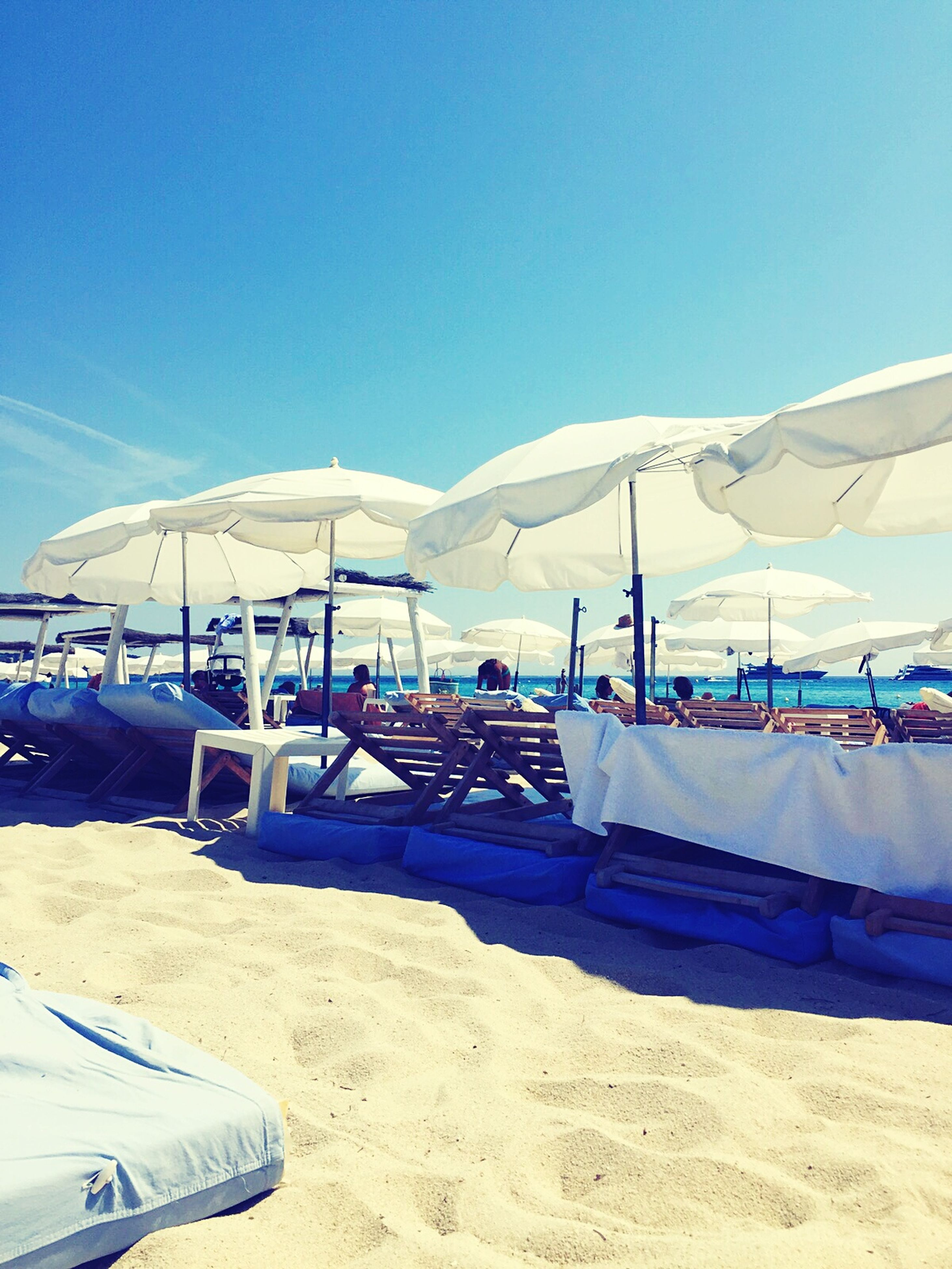 clear sky, sand, blue, beach, mountain, transportation, beach umbrella, tranquility, sunlight, tranquil scene, sky, vacations, landscape, nature, scenics, copy space, travel, day, mode of transport, parasol
