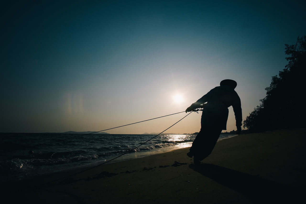 sea, silhouette, one person, nature, water, beach, real people, full length, sunset, men, beauty in nature, leisure activity, standing, scenics, horizon over water, vacations, outdoors, lifestyles, sky, sunlight, sand, adventure, one man only, day, only men, adult, people