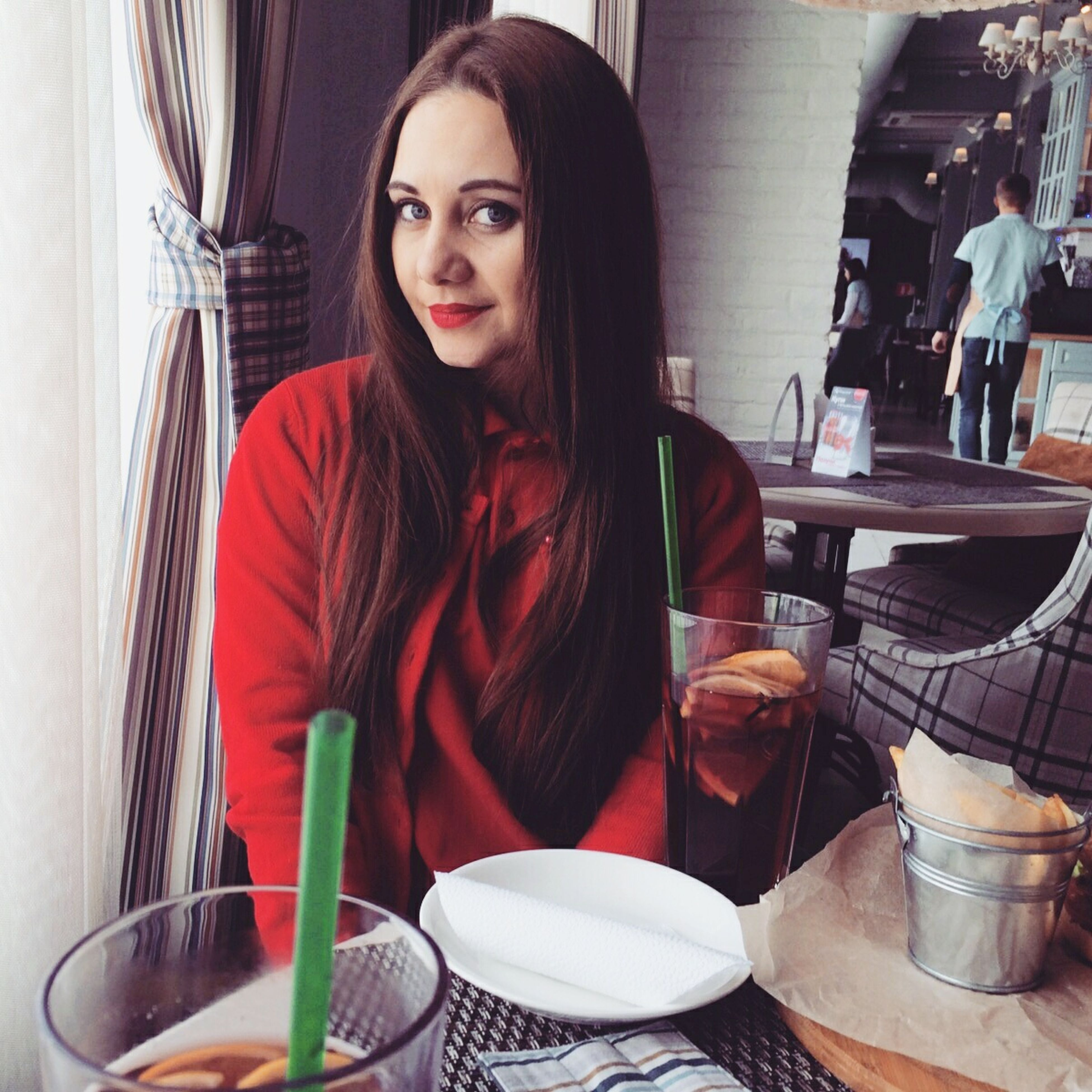 indoors, food and drink, drink, table, lifestyles, freshness, food, restaurant, sitting, young adult, leisure activity, casual clothing, refreshment, young women, person, front view, holding, plate