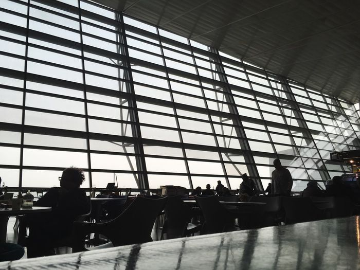 Indoors  Window Silhouette Travel Airport Real People Sitting Men Airport Departure Area Architecture Travel Destinations Transportation Building - Type Of Building Built Structure Day Women Seat Adult People