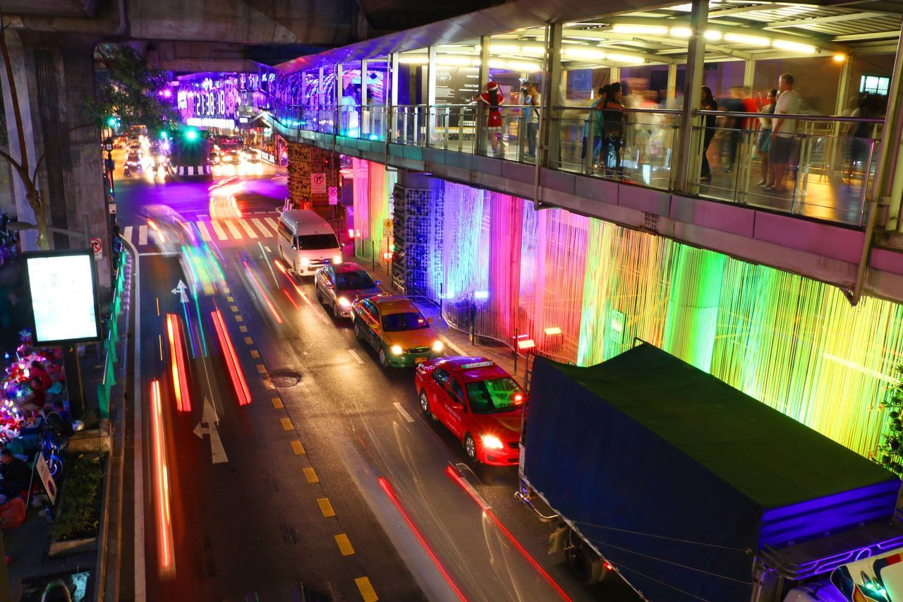 illuminated, night, transportation, land vehicle, mode of transport, car, city, traffic, street, architecture, road, blurred motion, long exposure, light trail, city life, building exterior, outdoors, nightlife, built structure, motion, neon, no people