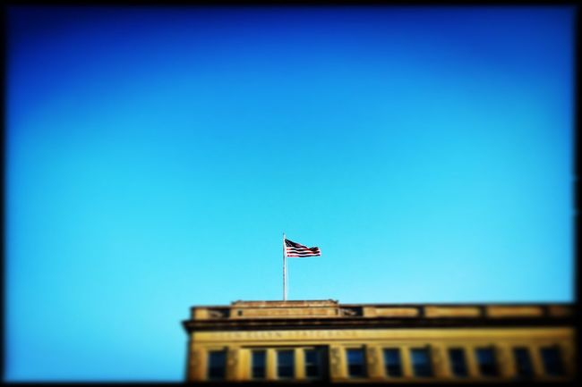 """Blue skies smilin' at me."" American Flag Photooftheday Photojournalism Documentary Reportage Color Building Exterior Building Architecture IPhoneography"