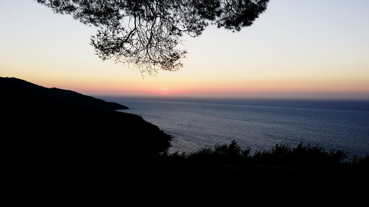 sunset, beauty in nature, sea, scenics, nature, tranquil scene, orange color, tranquility, silhouette, water, sky, tree, horizon over water, no people, outdoors, sun, beach, mountain, clear sky, day