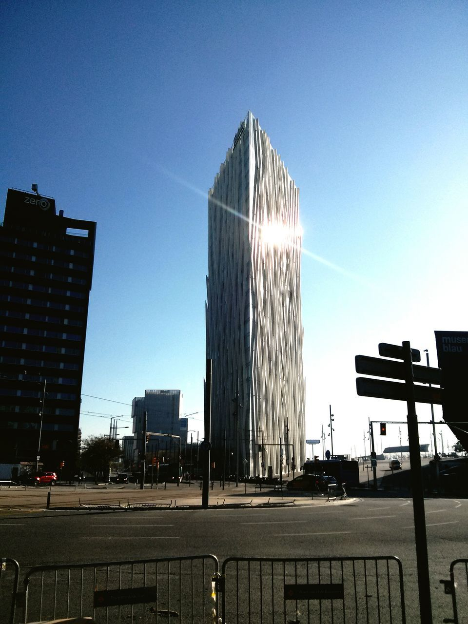 architecture, built structure, building exterior, clear sky, outdoors, city, sky, sunlight, day, blue, skyscraper, no people, modern