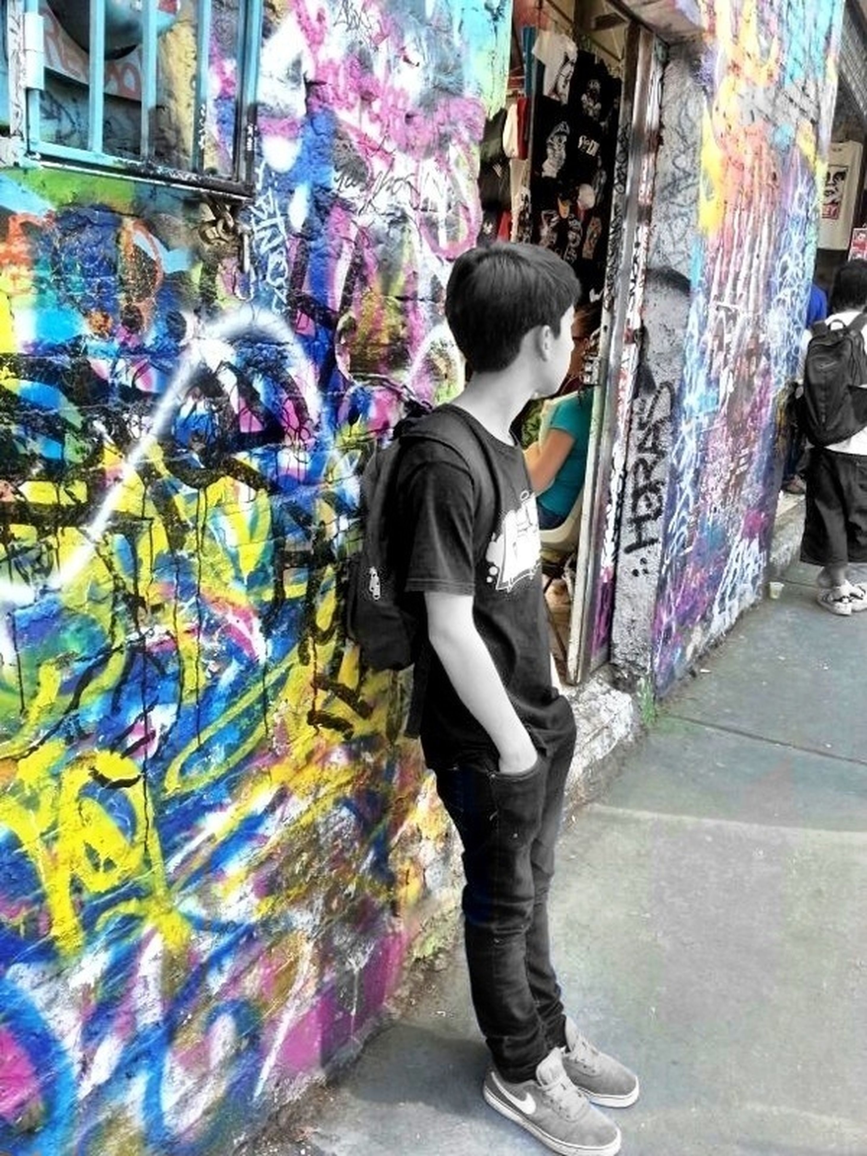 full length, casual clothing, lifestyles, rear view, built structure, building exterior, architecture, leisure activity, graffiti, street, walking, multi colored, standing, childhood, men, wall - building feature, person, boys