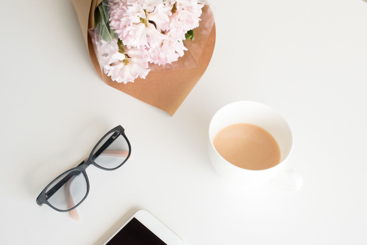 Pink hyacinth flowers, glasses, smart phone and cup of tea on white table from above Close-up Cup Of Tea Day Directly Above Eyeglasses  Flatlay Flower Flowers Freshness High Angle View Indoors  No People Smart Phone Table White Background