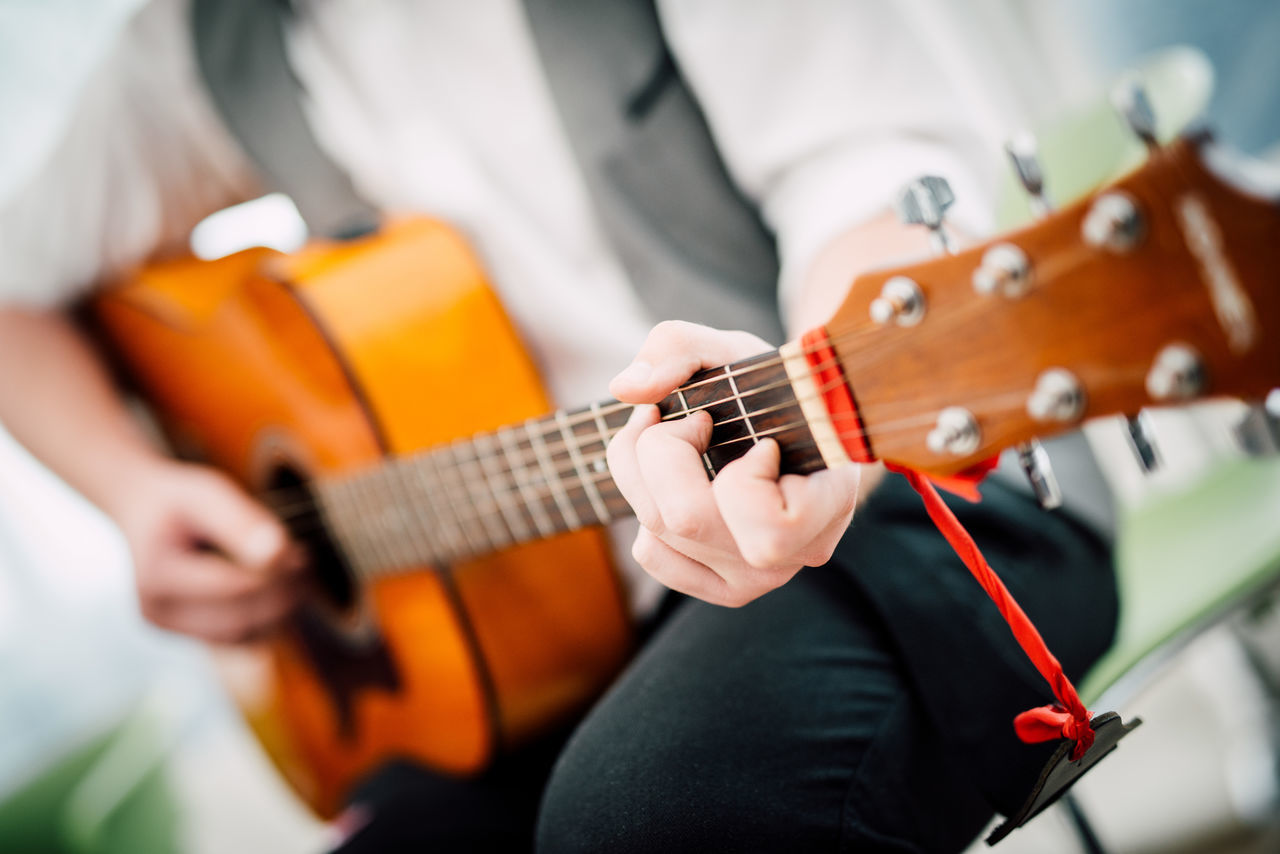 Adult Adults Only Arts Culture And Entertainment Close-up Guitar Guitarist Holding Human Hand Men Midsection Music Musical Instrument Musical Instrument String Musician One Person Only Men People Playing Plucking An Instrument Popular Music Concert Skill  String Instrument Young Adult