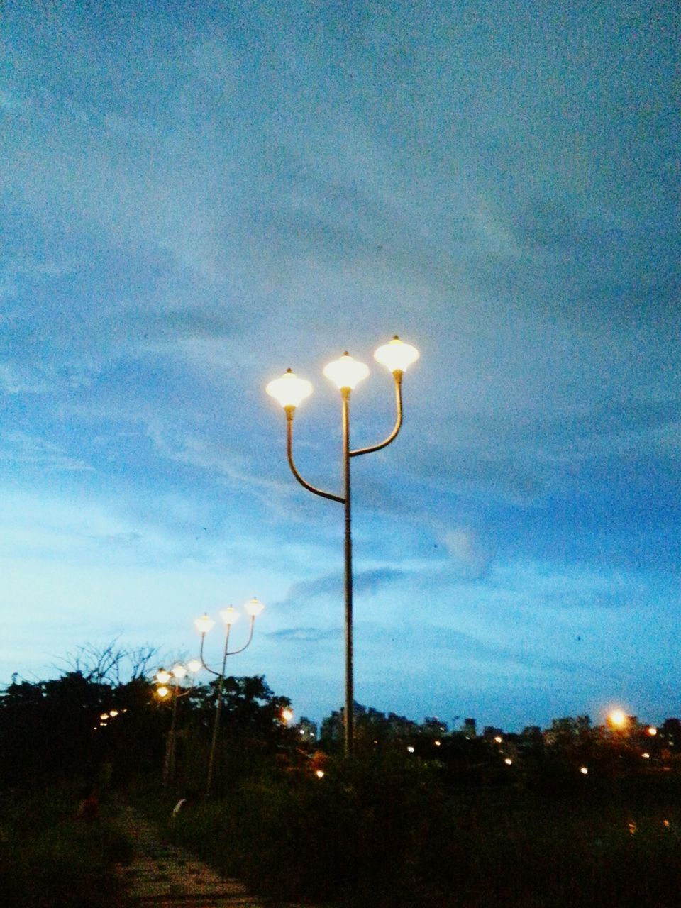 illuminated, lighting equipment, street light, night, dusk, sky, cloud - sky, no people, electricity, low angle view, outdoors, nature, blue, floodlight, beauty in nature, tree
