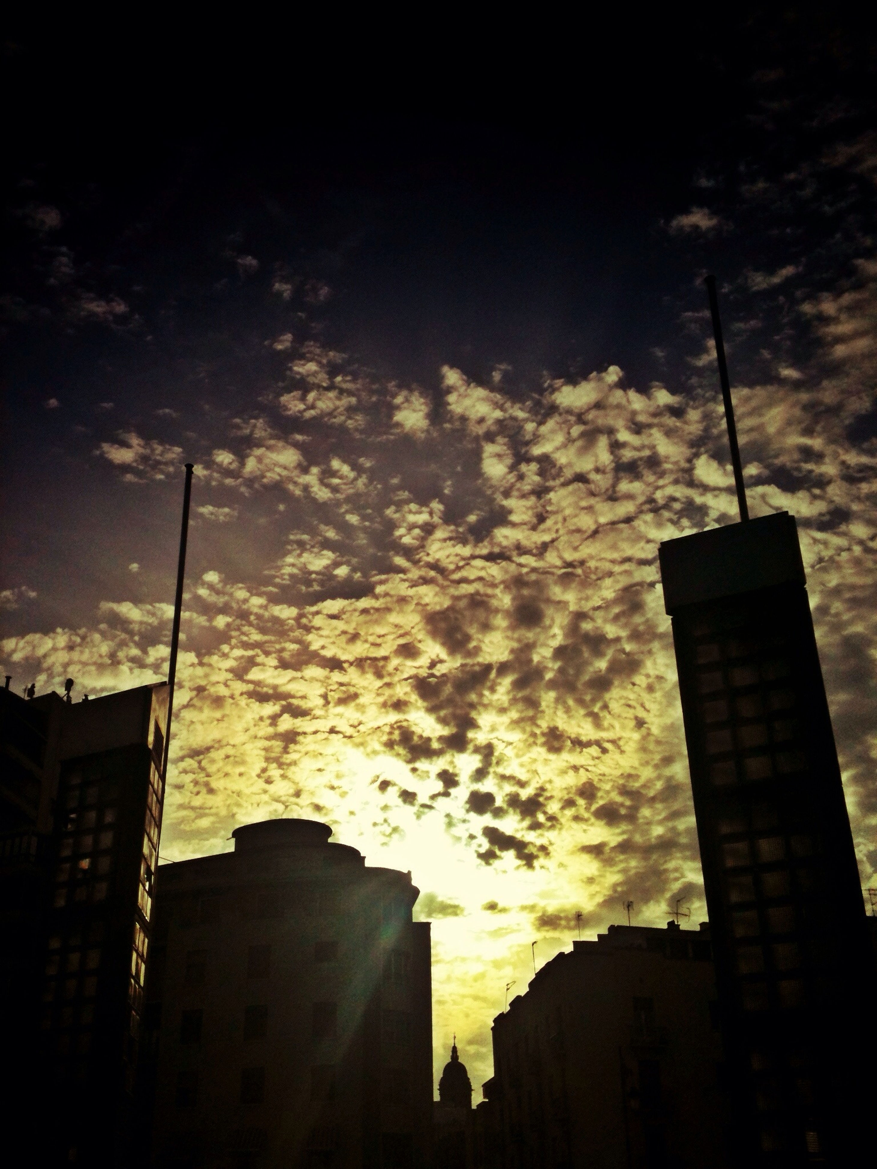 building exterior, architecture, built structure, low angle view, sky, silhouette, sunset, city, cloud - sky, street light, building, residential building, cloudy, tall - high, dusk, tower, residential structure, cloud, outdoors, no people