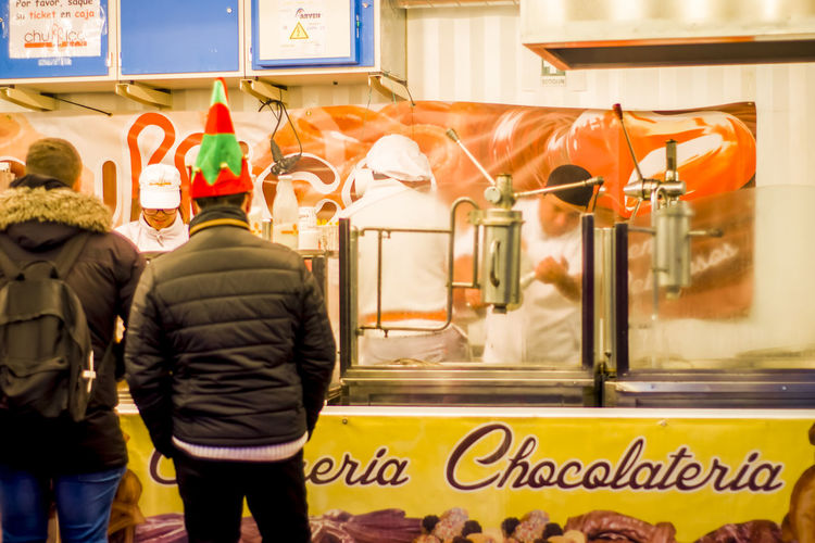 People buying Churros and Chocolate at a stall in Opera Madrid Spain. Chocolate Churro Churros City Life Tradition Working Candid Chirstmas Day Editorial  Food Men Occupation People Real People Rear View Stall Street Street Food Text Women