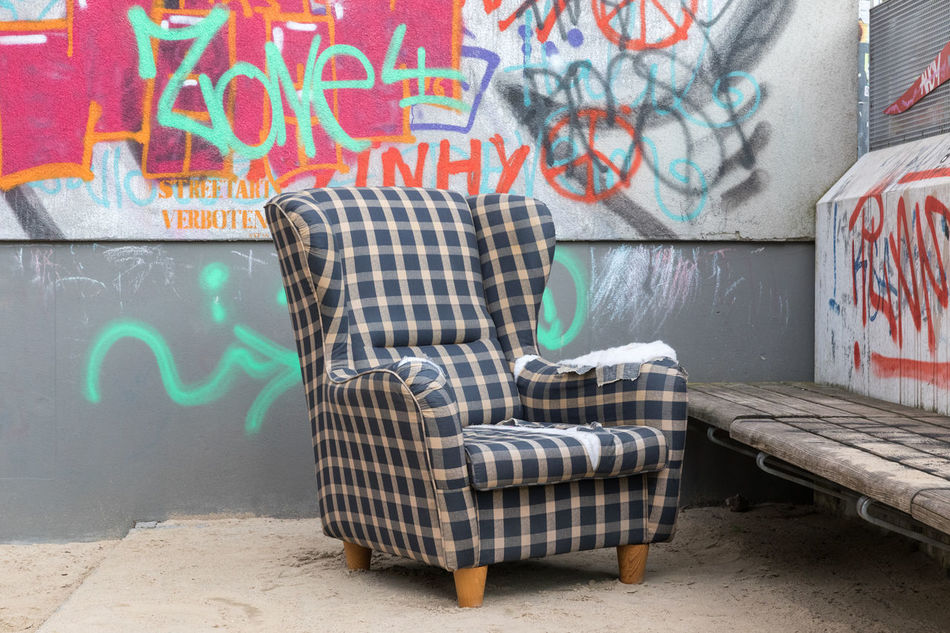 Damaged armchair next to a sandbox on a public playground Abandoned Architecture Armchair Bench Building Exterior Built Structure Chair Checked Pattern City Deterioration Garbage Graffiti Lifestyles Multi Colored No People Old Outdoors Pattern Playground Ruined Sand Sandbox Street Art Wall - Building Feature Wood - Material