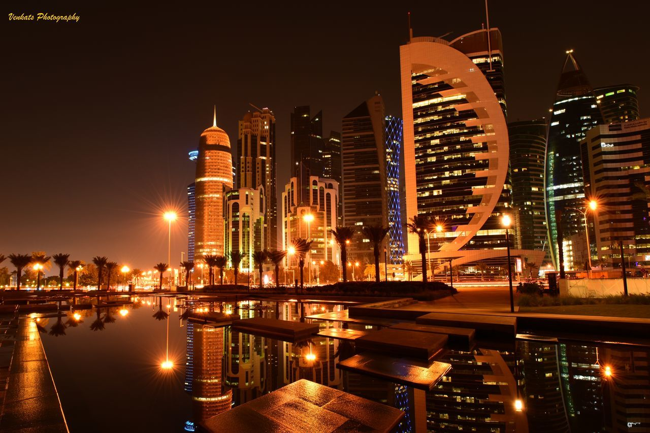 illuminated, night, architecture, building exterior, built structure, water, city, modern, skyscraper, reflection, waterfront, no people, cityscape, outdoors, travel destinations, urban skyline, clear sky, sky, nautical vessel
