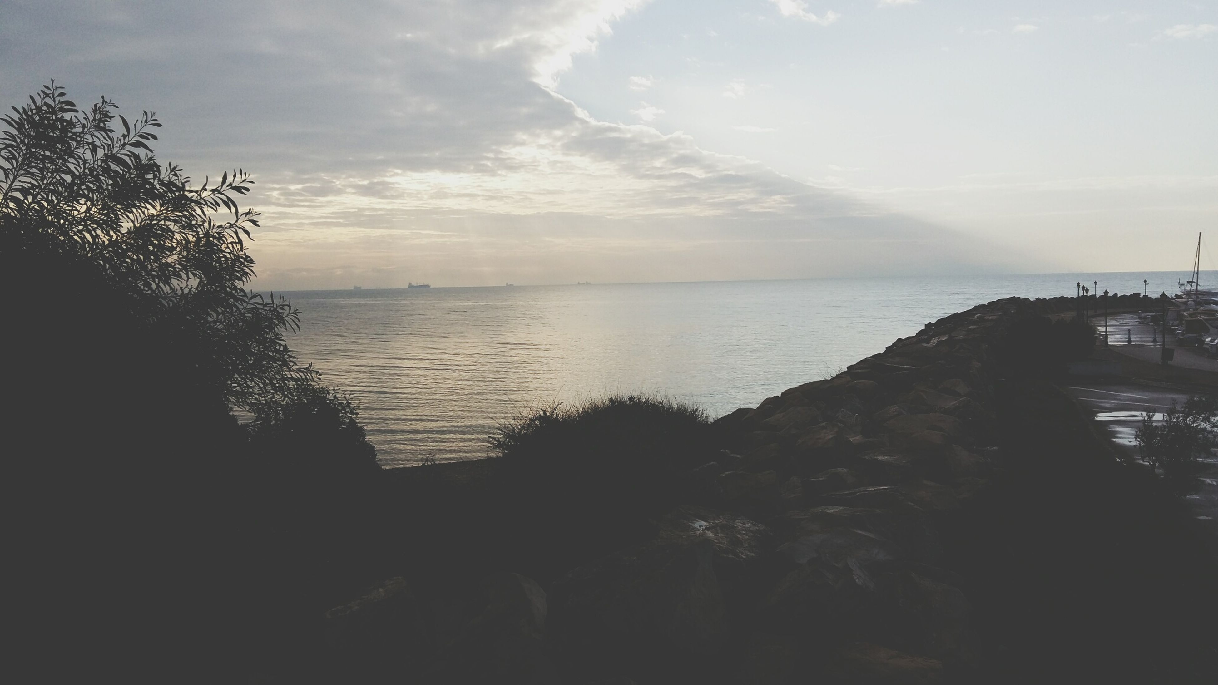 sea, water, horizon over water, sky, tranquil scene, scenics, tranquility, beauty in nature, beach, nature, silhouette, shore, idyllic, sunset, cloud - sky, tree, cloud, outdoors, calm, remote