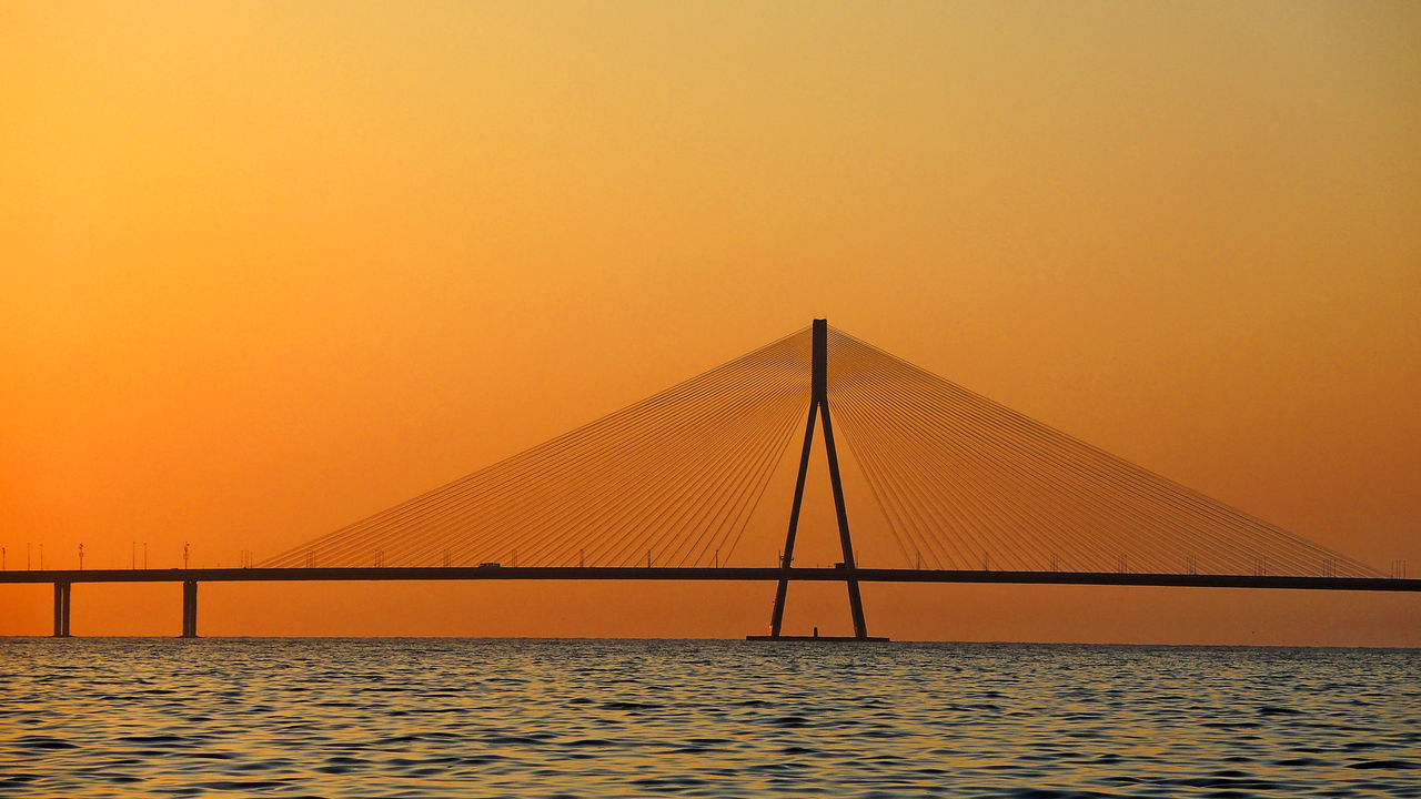 sunset, suspension bridge, bridge - man made structure, water, connection, orange color, sea, sky, outdoors, no people, scenics, nature, holiday, bridge, beauty in nature, architecture, clear sky, horizon over water, day