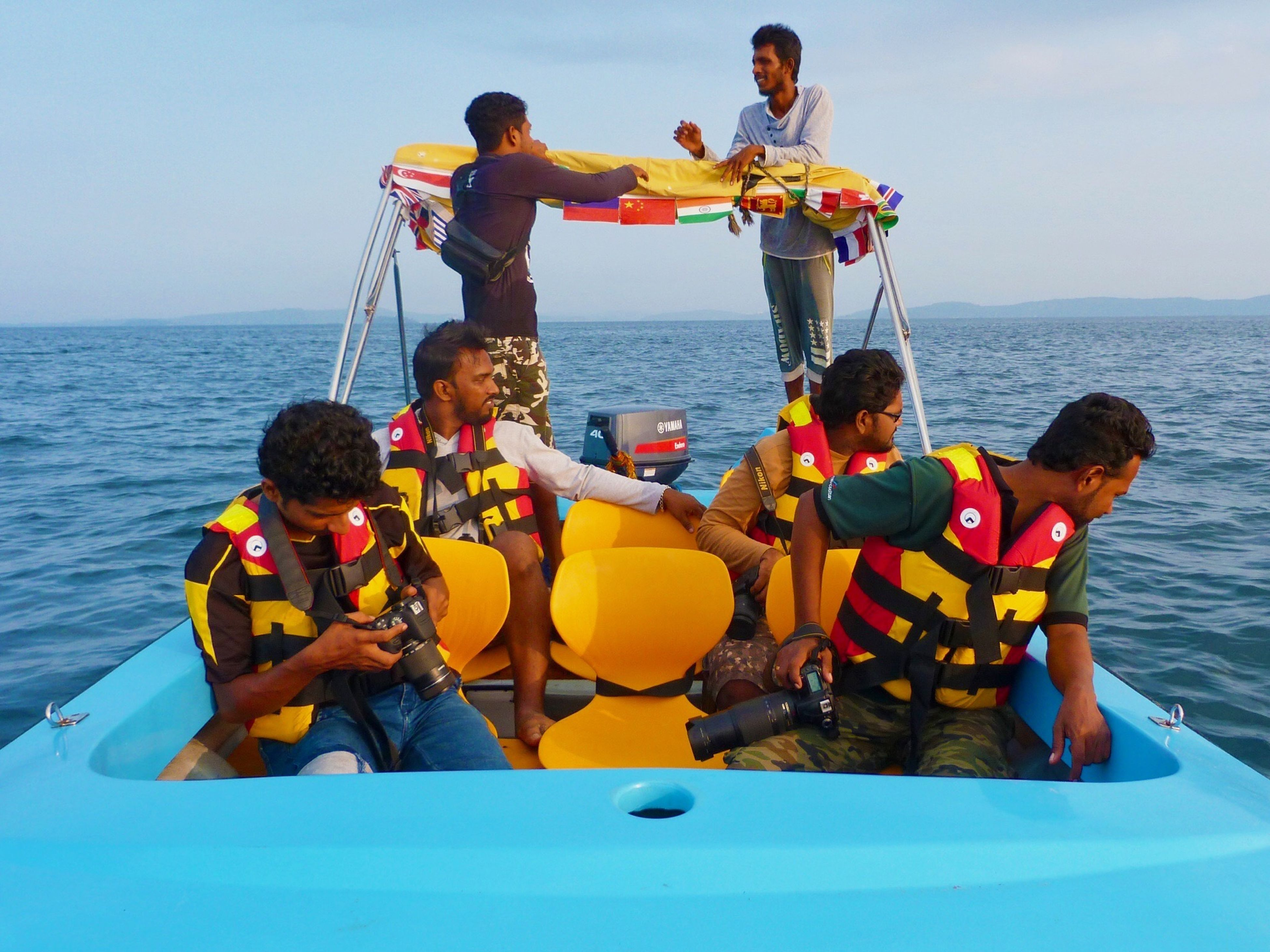sea, water, leisure activity, real people, nautical vessel, outdoors, men, sky, day, horizon over water, sitting, beach, togetherness, boys, childhood, standing, women, nature, friendship