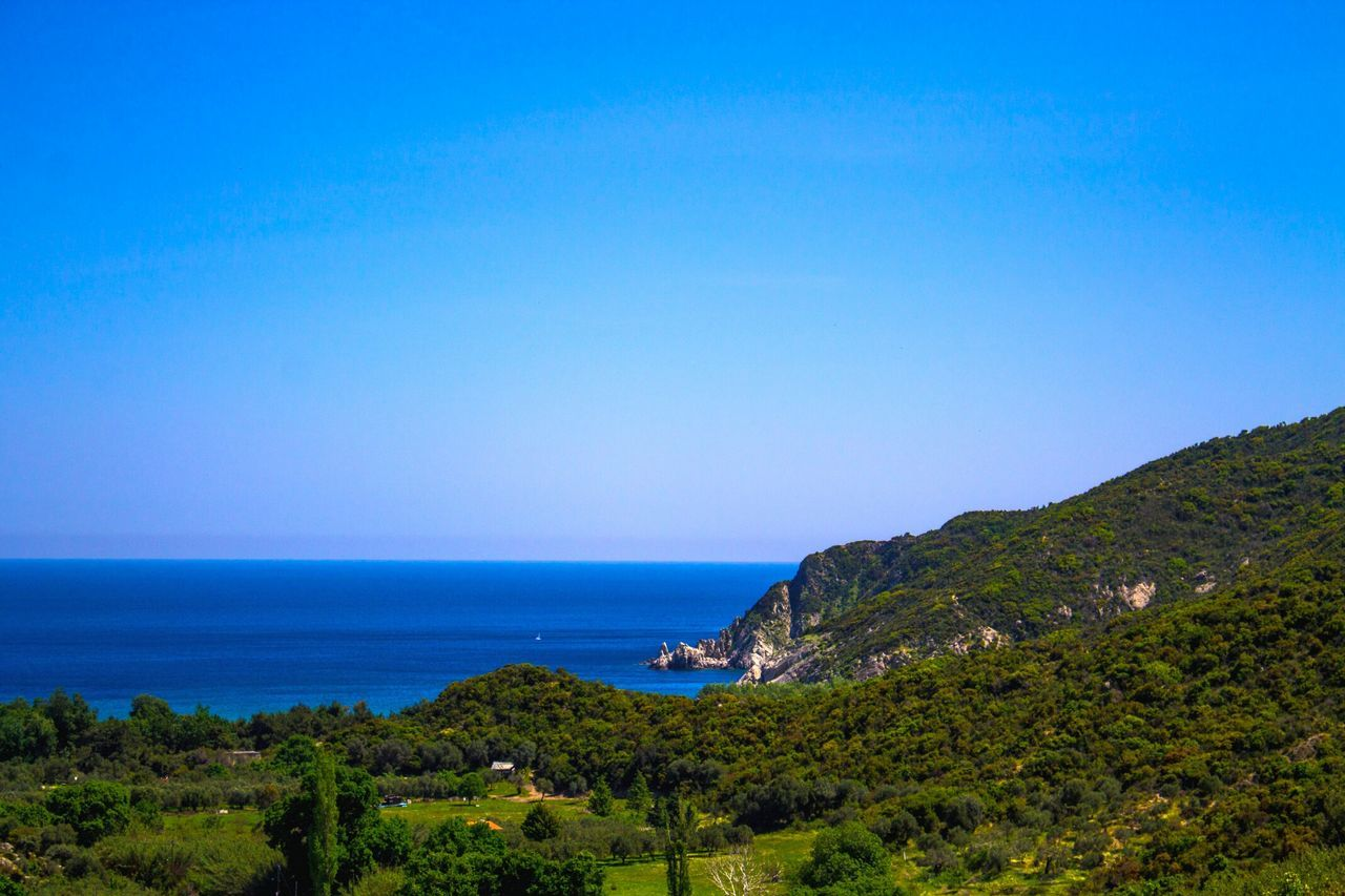 sea, blue, beauty in nature, nature, scenics, tranquil scene, water, tranquility, clear sky, horizon over water, outdoors, no people, mountain, day, landscape, sky, scenery, grass, tree