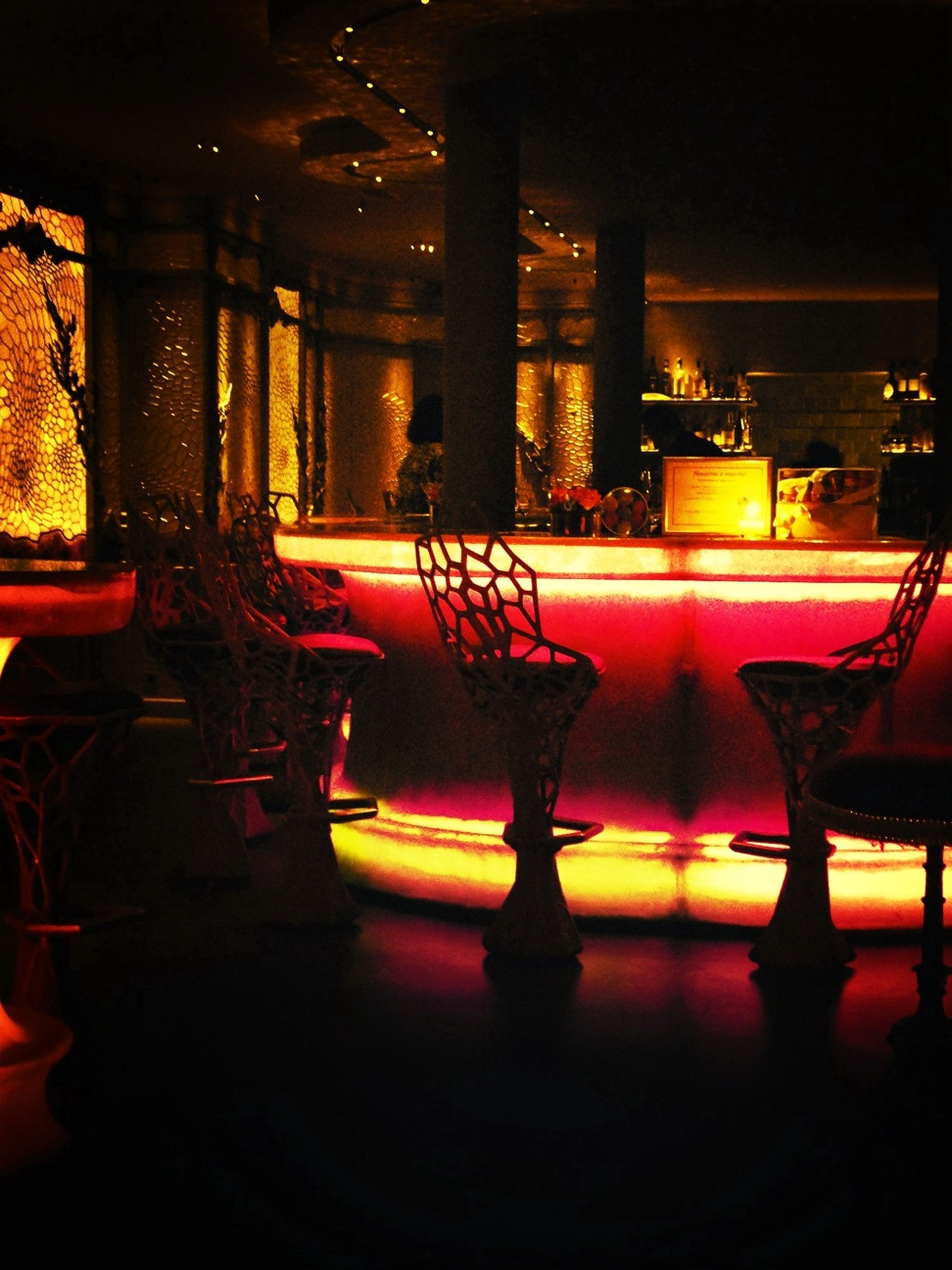 illuminated, night, chair, built structure, architecture, absence, empty, lighting equipment, indoors, table, dark, restaurant, building exterior, light - natural phenomenon, reflection, no people, seat, light, in a row, city