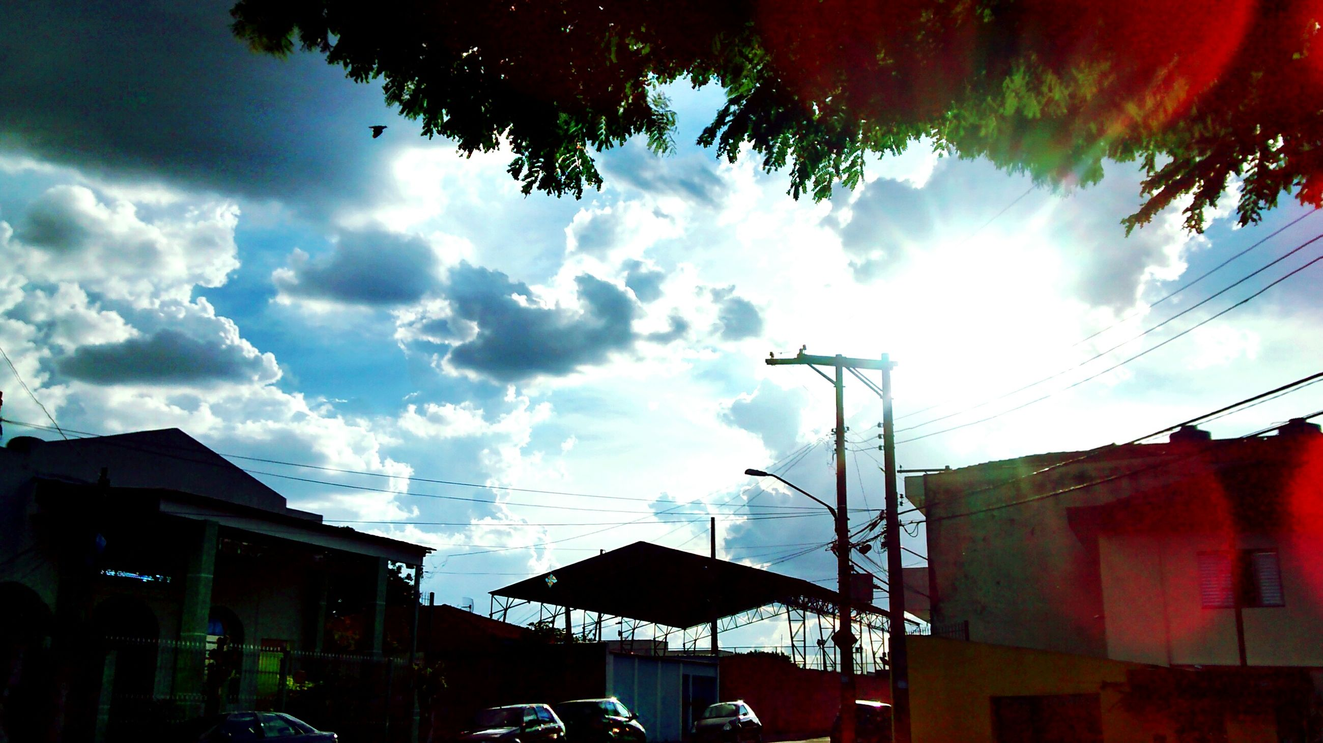 building exterior, architecture, built structure, sky, low angle view, cloud - sky, residential building, residential structure, house, cloudy, power line, building, cloud, city, sunlight, cable, outdoors, no people, residential district, day