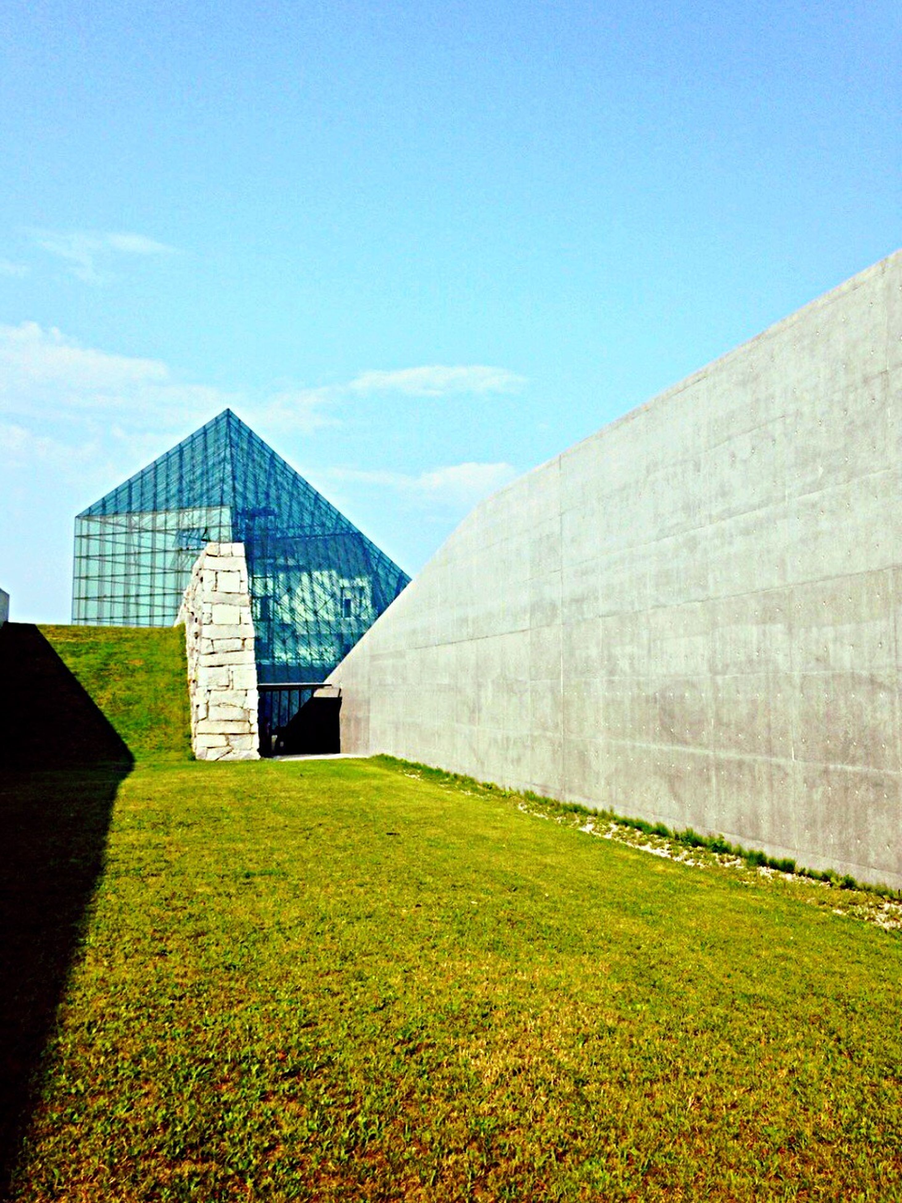 architecture, built structure, building exterior, grass, sky, tower, blue, sunlight, day, clear sky, green color, field, travel destinations, famous place, outdoors, no people, tree, copy space, low angle view, nature