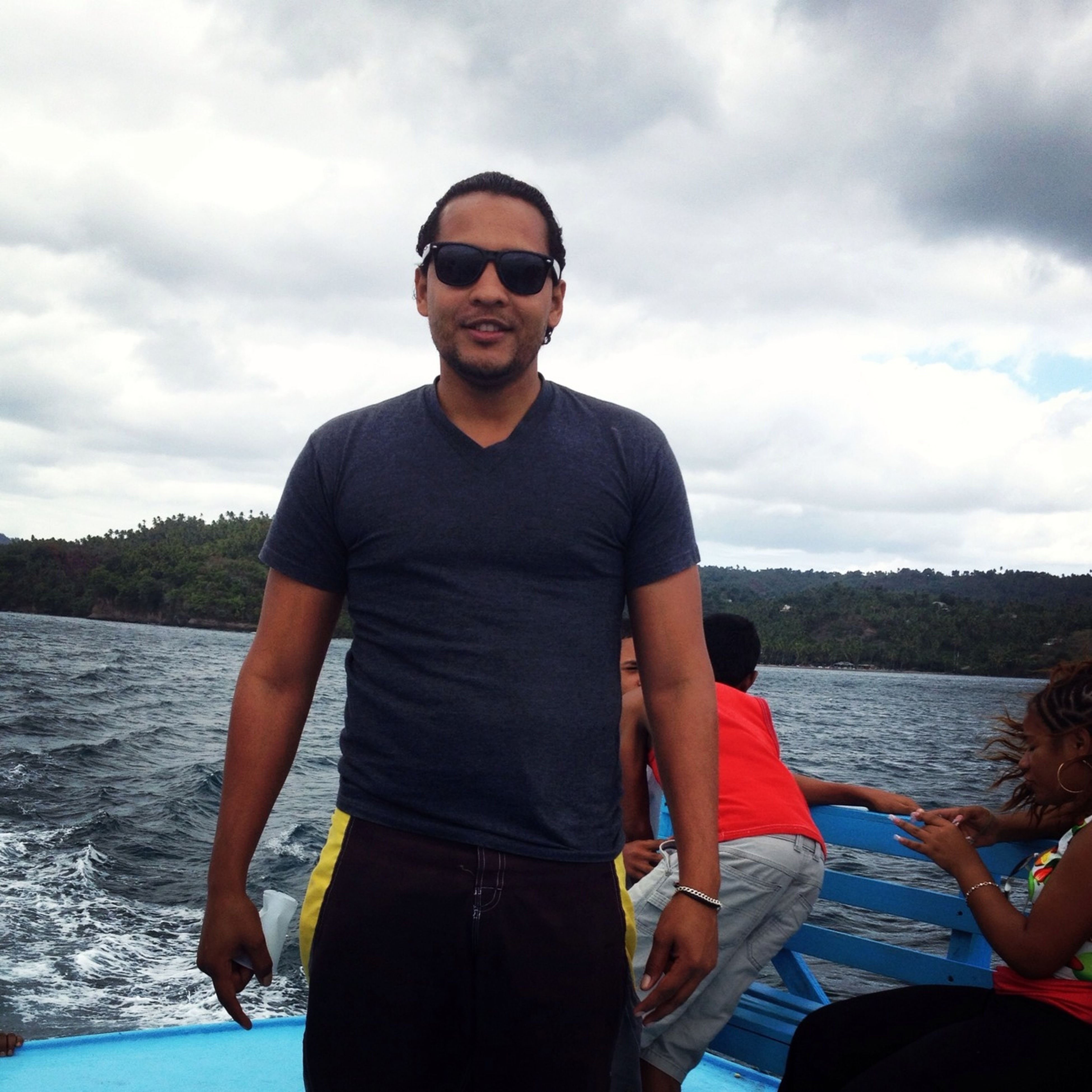 lifestyles, looking at camera, portrait, sky, person, casual clothing, leisure activity, young men, cloud - sky, sunglasses, water, front view, young adult, standing, three quarter length, smiling, waist up, cloud