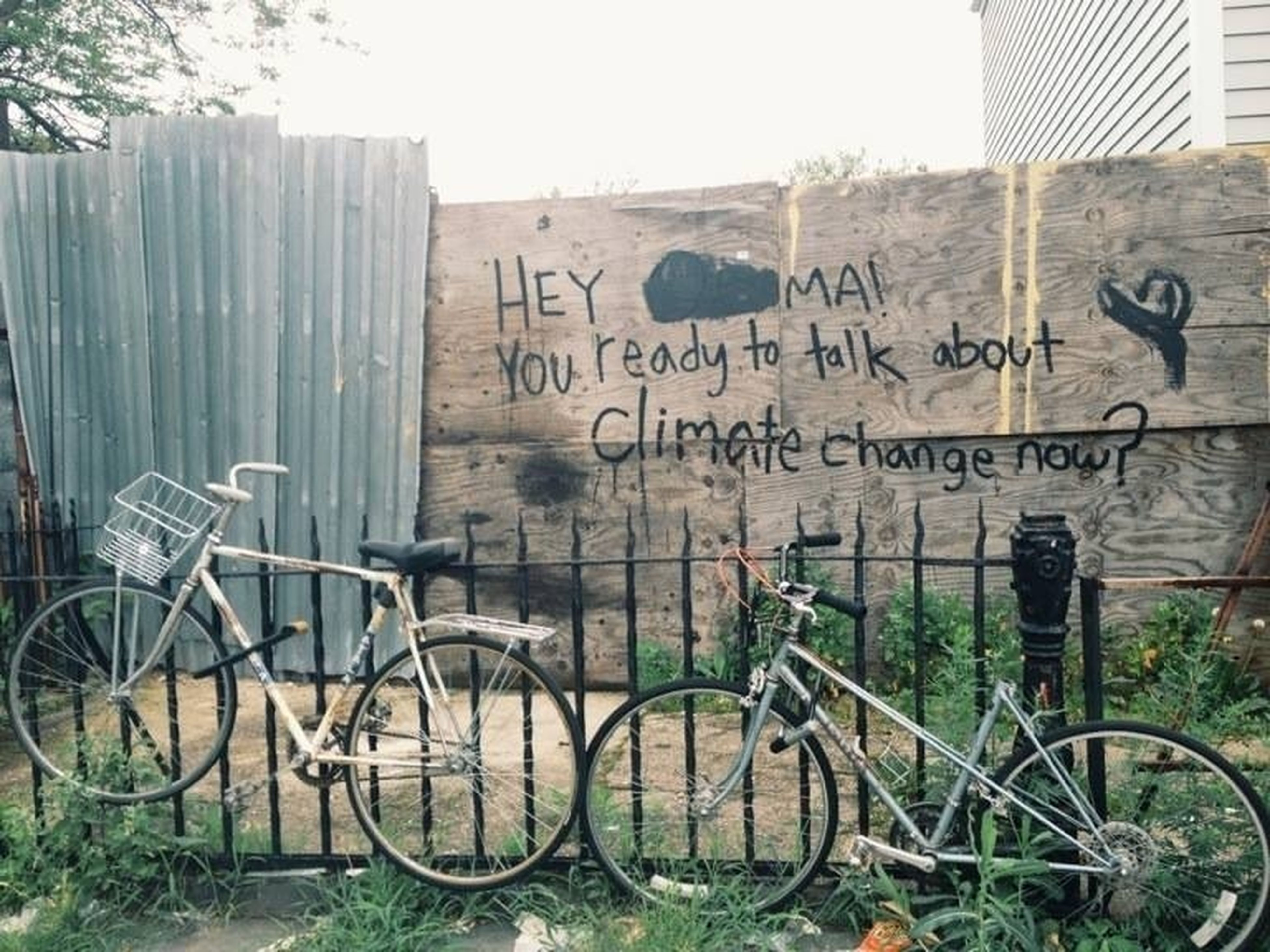 bicycle, architecture, transportation, built structure, text, building exterior, mode of transport, land vehicle, wall - building feature, parked, stationary, western script, parking, day, no people, graffiti, outdoors, communication, wall, fence