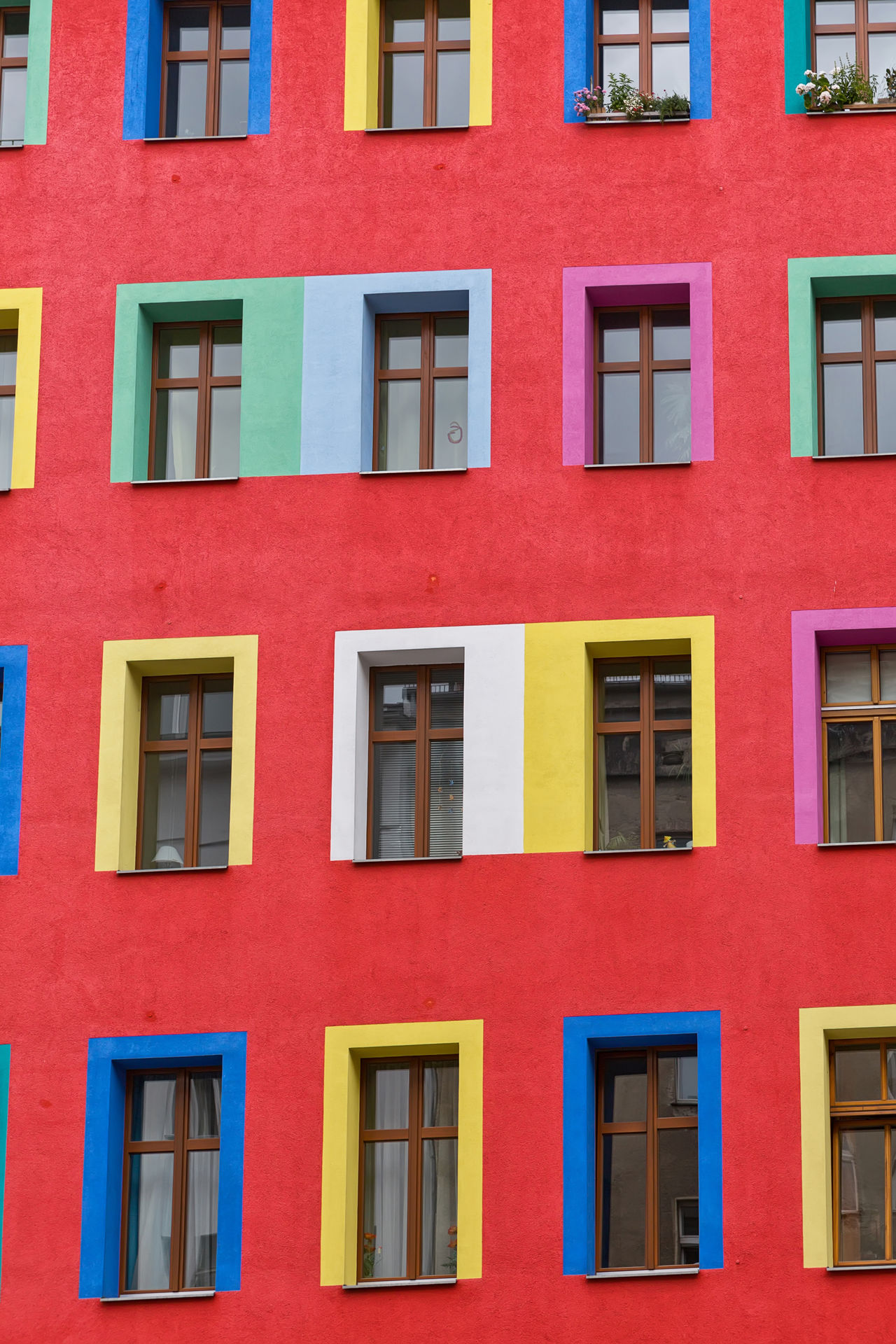 Red rendered facade of an aparemtent building. Each window is painted in bright colours to give a colourful look to the city Architecture Architecture Backgrounds Building Exterior Built Structure City Colourful Day Facade Building Facade Detail Facades Façade Full Frame Multi Colored No People Outdoors Red Red Residential  Residential Building Window