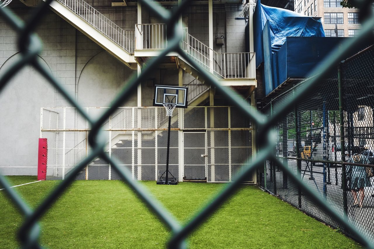 Basketball Hoop Against Stairs Seen From Chainlink Fence