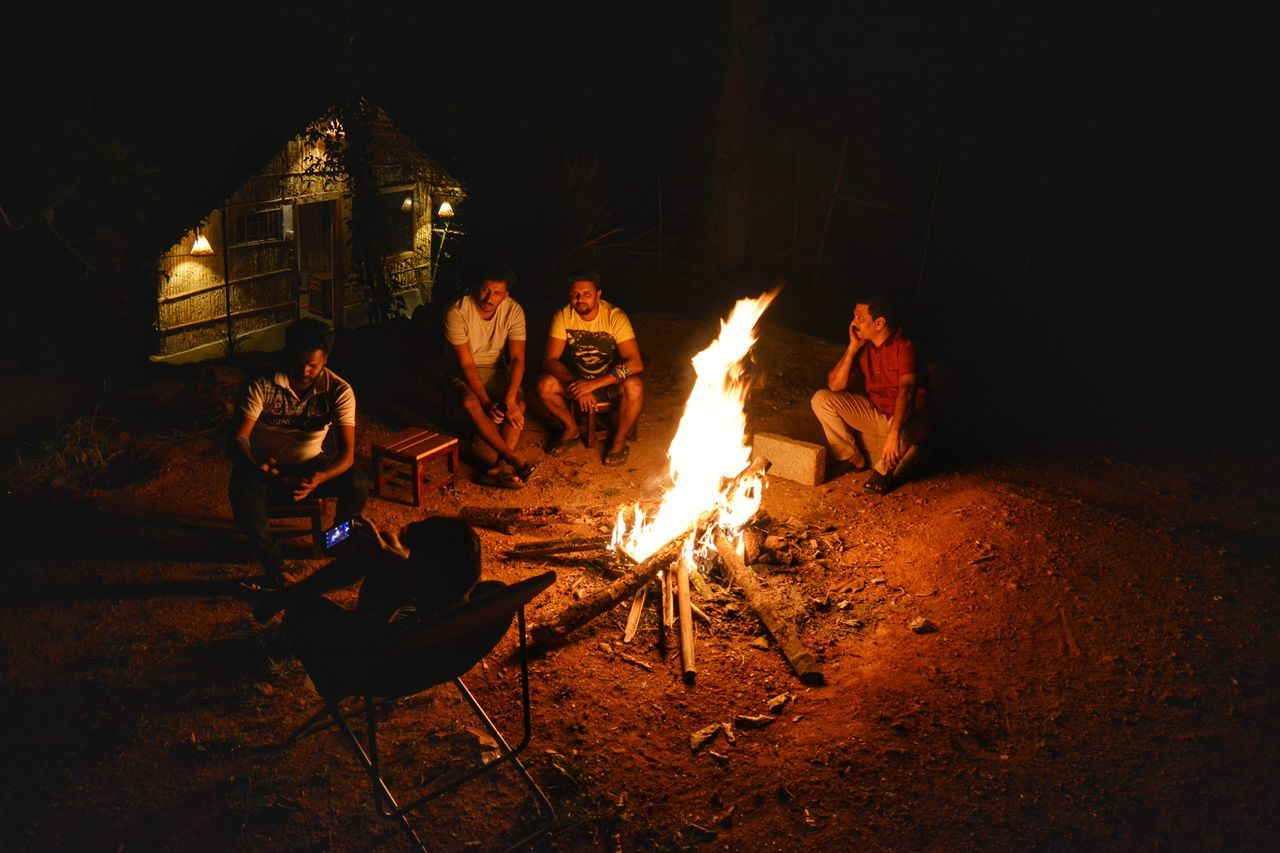 High Angle View Of People Sitting At Campsite During Night